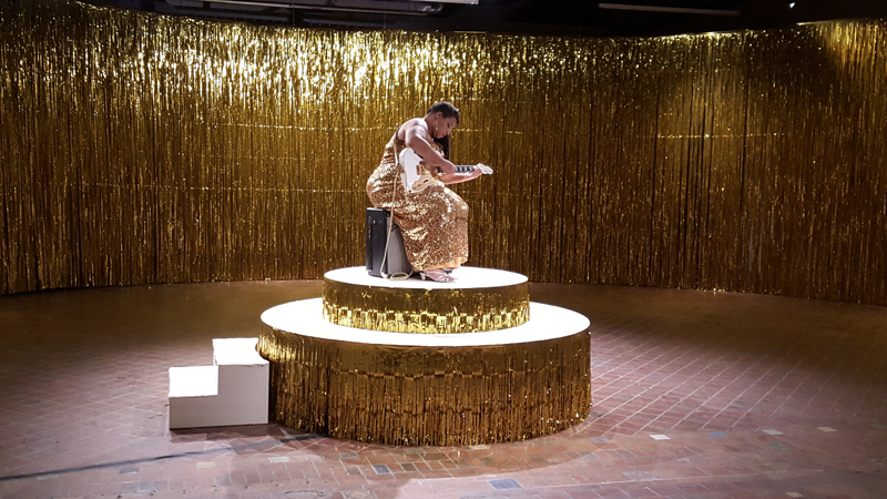 A room is lined with floor to ceiling shimming, golden curtains of streamers. In the middle of the room a circular platform, also draped on it's edges in the gold streams, holds a live woman, clad in a shimmery golden sequin dress. She sits on a speaker, leaned over a white guitar she is preparing to play.