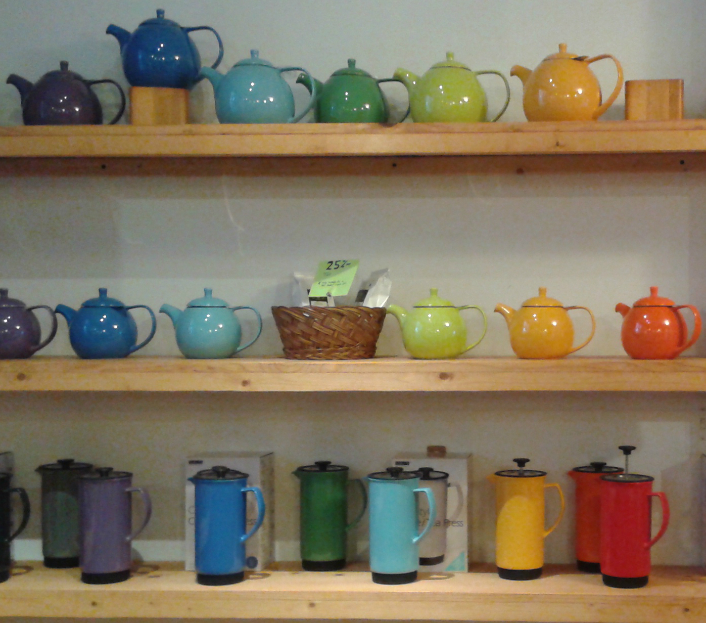Several colorful teapots sit on a shelf in Socra-tea.