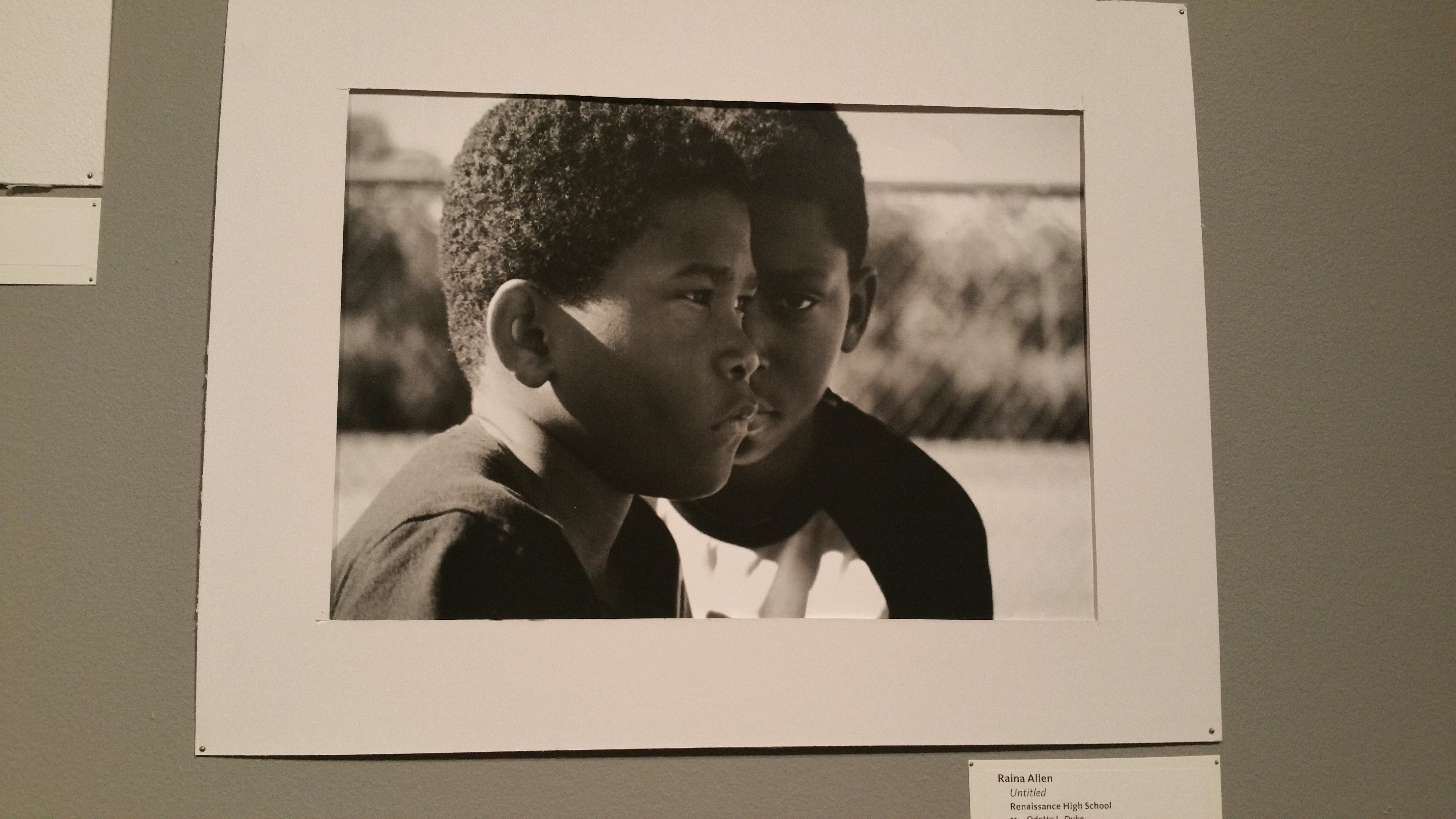 Black and white close up photo of two young African American boys with short hair, one is facing the camera with half of his face covered by the other boy who is facing sideways.