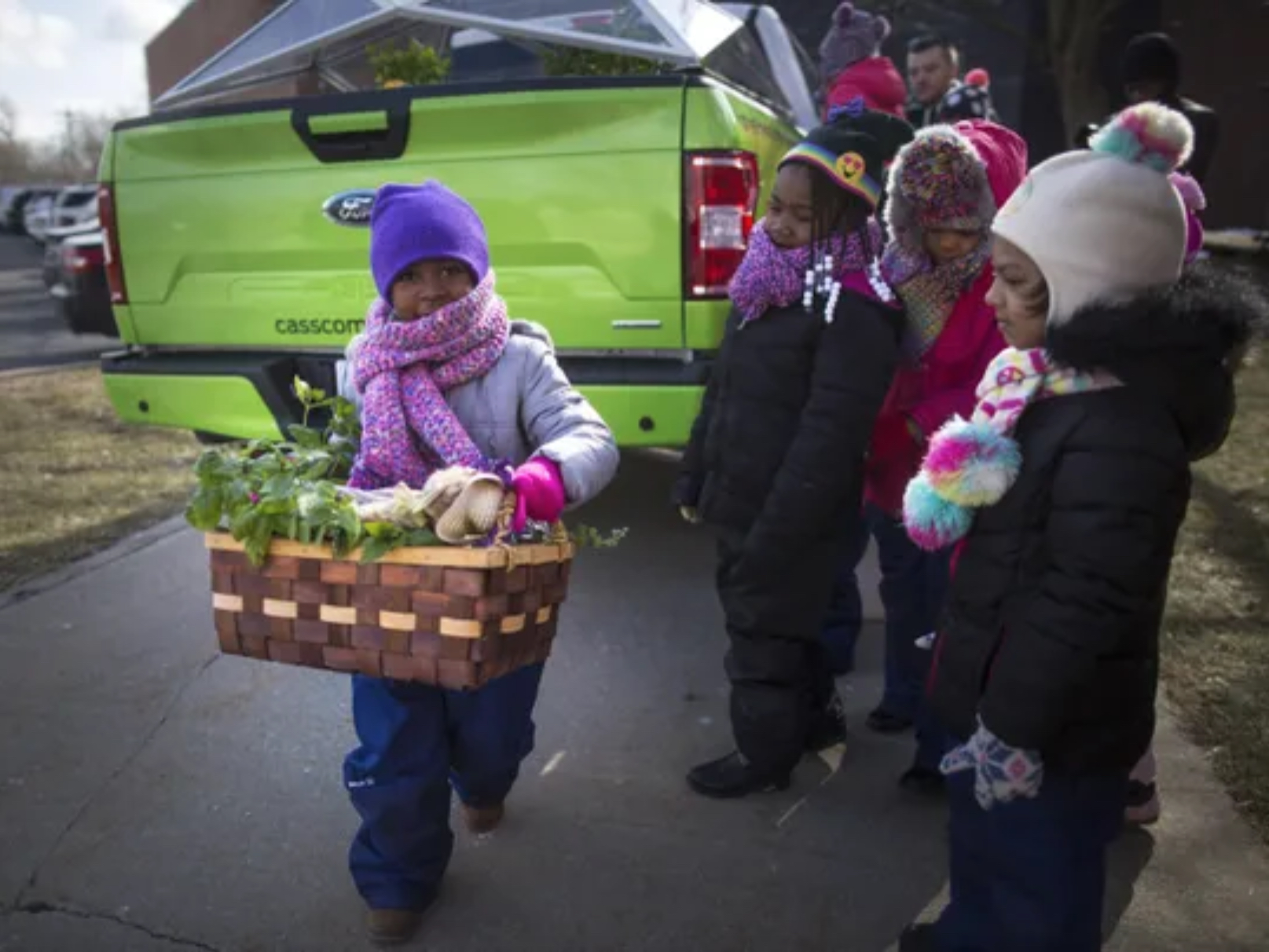A child carries produce and plants from a Cass Community Social Services F-150 at a local Detroit school