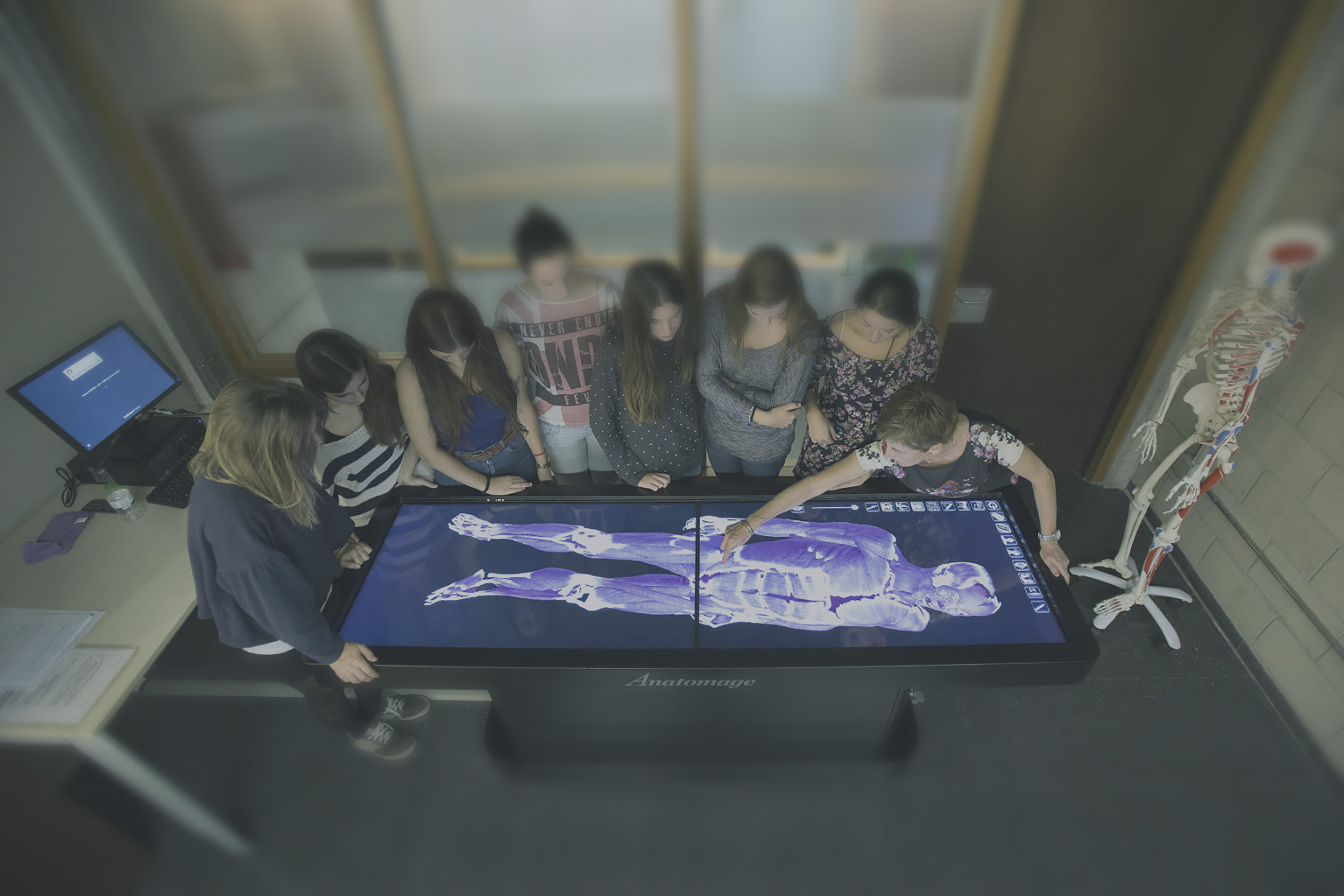 Students standing around the anatomage table examining the anatomy of human body through a touchscreen that allows them to zoom in and move the 3D figure of the human body.
