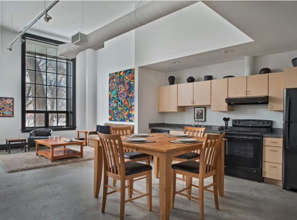 Modern kitchen in Artspace lofts with kitchen table and chairs in an open floor layout.