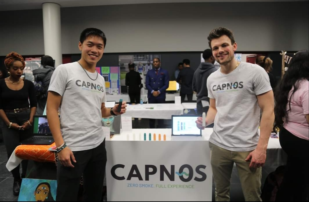 Two students in front of display for their Social Venture challenge