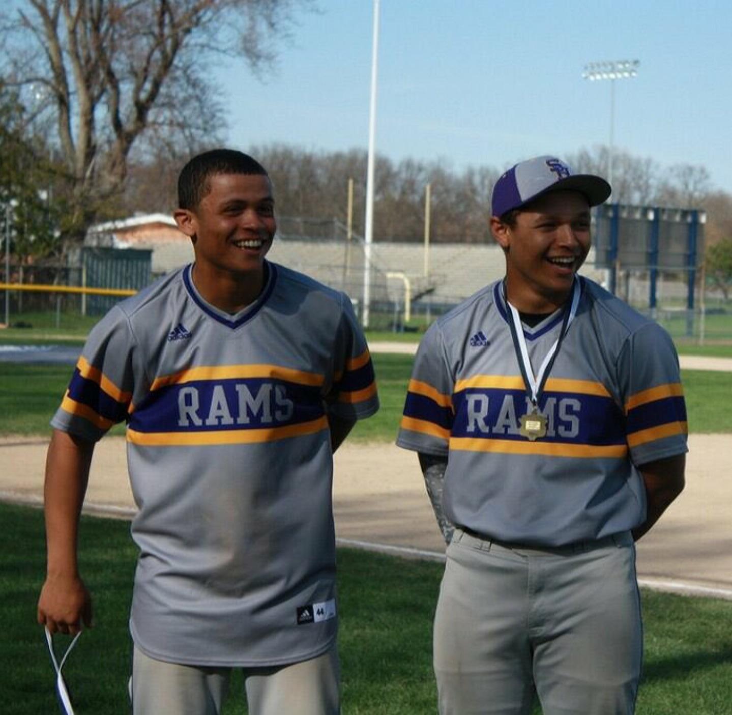 Two men pose for a photo, smiling, wearing baseball uniforms.