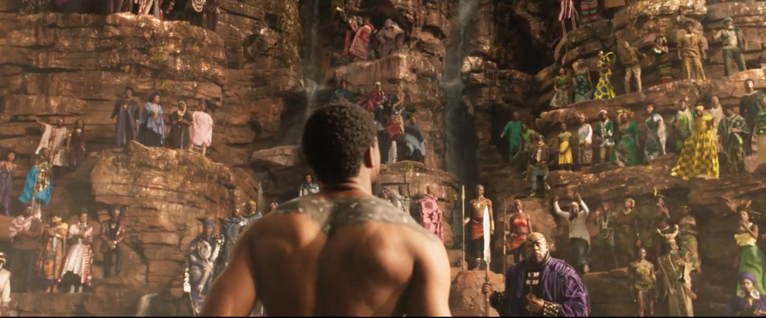 Scene from Black Panther of ritual fight showing actor Chadwick Bozeman looking up cliff where tribal leaders watch courtesy Marvel Studios