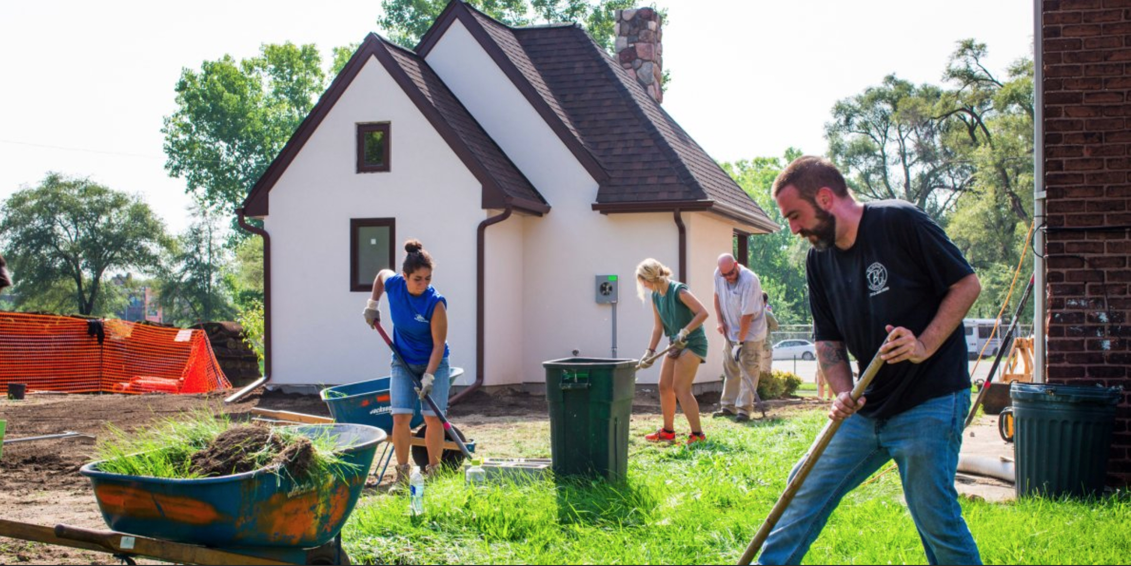Cass Community Services staff and volunteer help beautify one of the tiny homes in Detroit