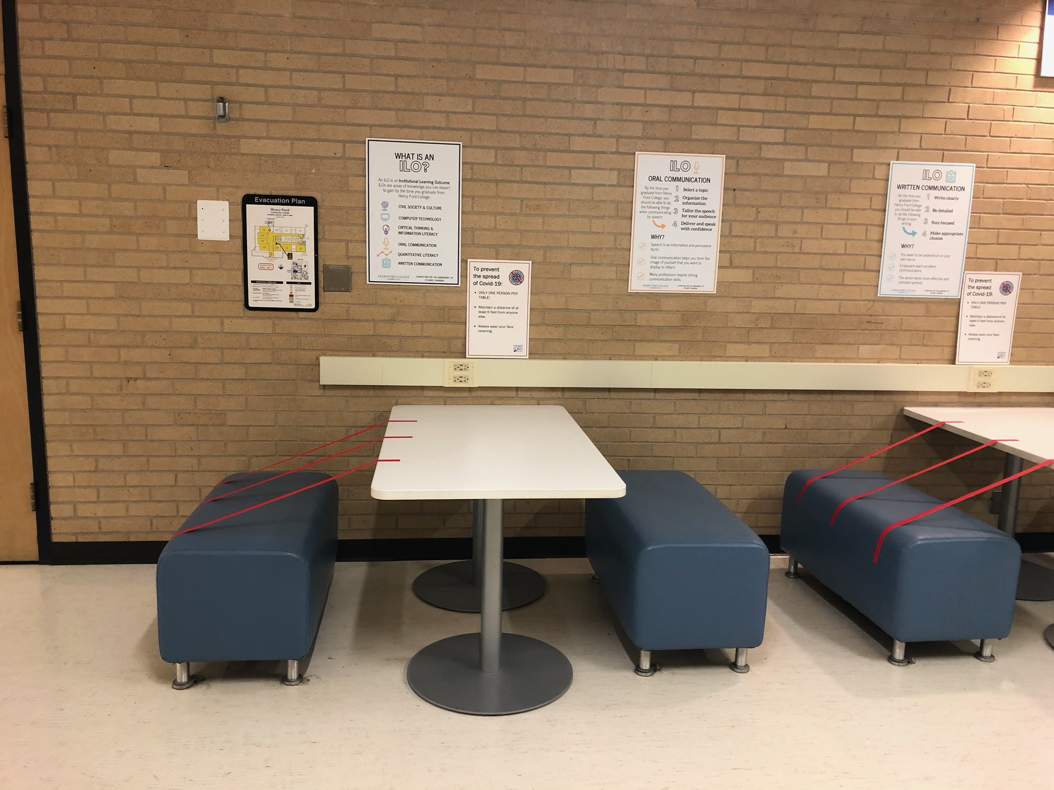 Chairs outside of biology classroom that are sectioned off with red colored tape to facilitate social distancing measures. Sign to display protocols to help prevent virus spread. Photo taken by Ms. Alice Hull