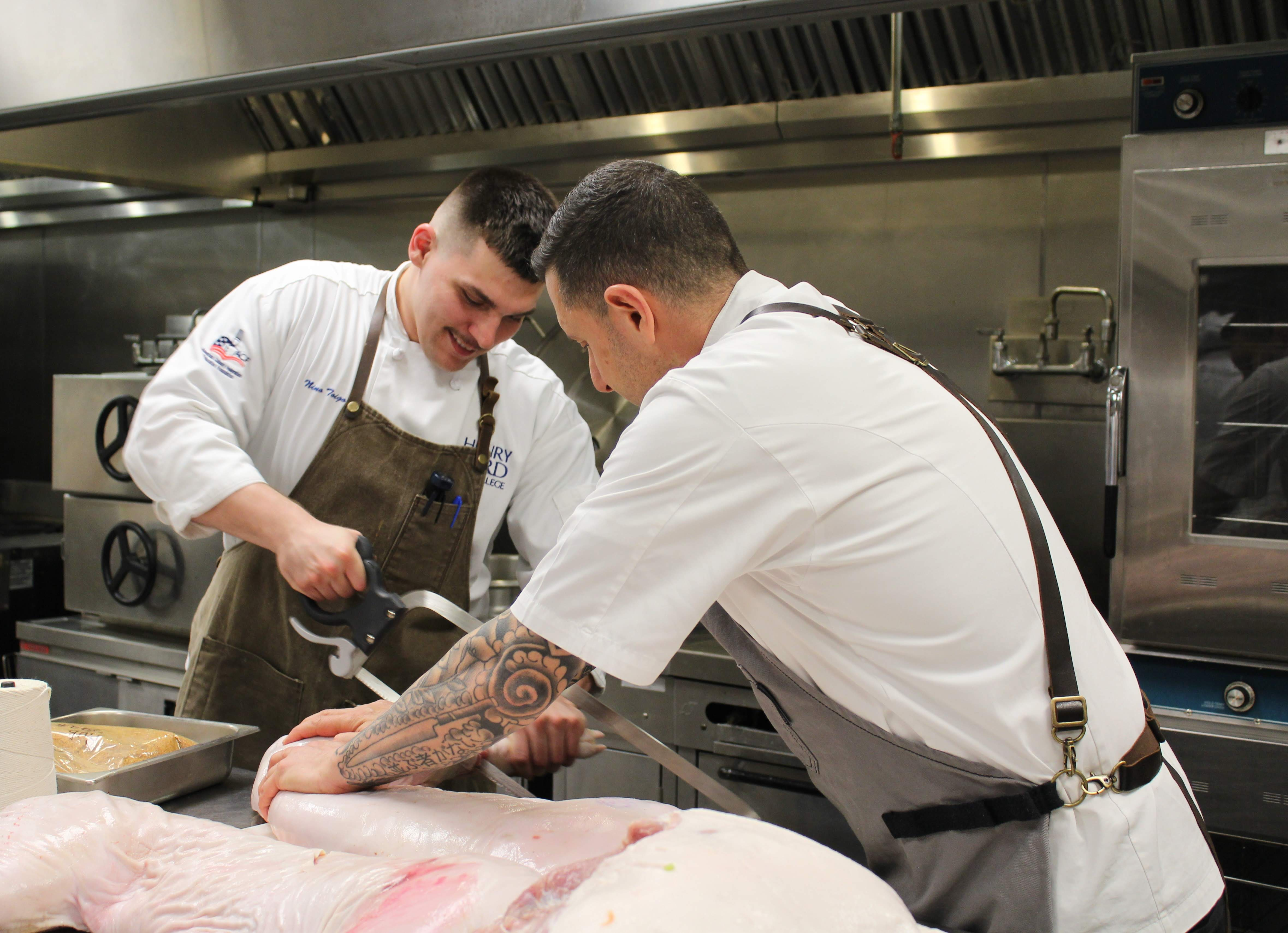 Chef Cosenza instructing Sous Chef Nino Toigo on butchering techniques