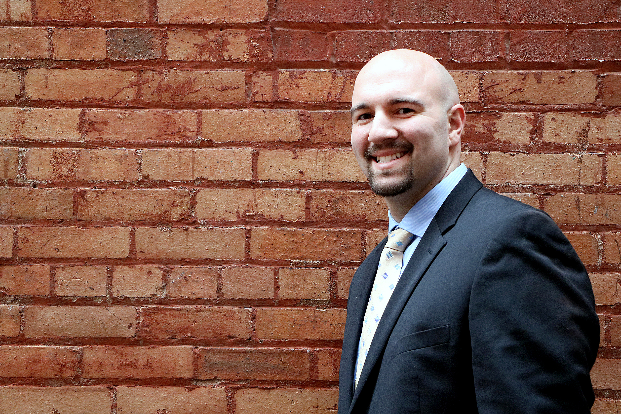 Photo of Anthony Ianni wearing a suit and tie outside of a building at Henry Ford College