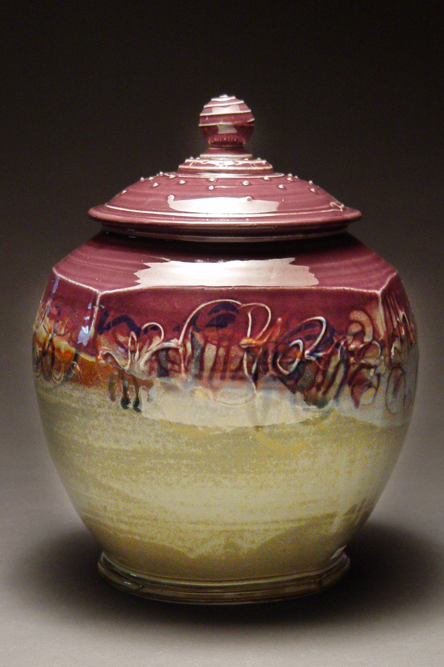 Clay jar with a lid glazed purple and beige by David Nelson.
