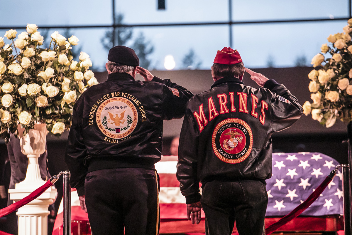 Two men wearing military jackets salute John Dingell Jr at funeral service in Dearborn, Michigan Feb 19, 2019 Photo by Joshua Tufts