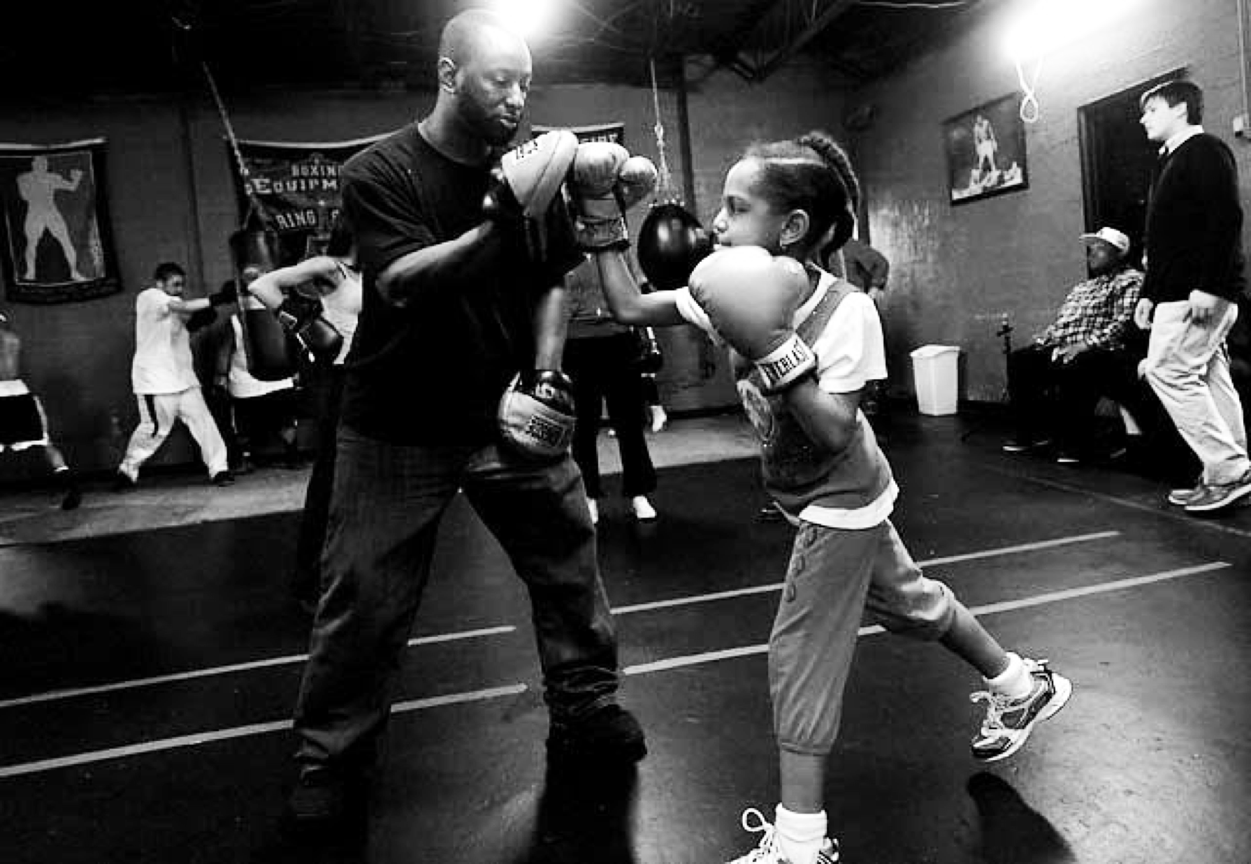 Khali Sweeney stands in the gym, helping a young female child boxer work her gloves. There are boxers working on equipment in the background.