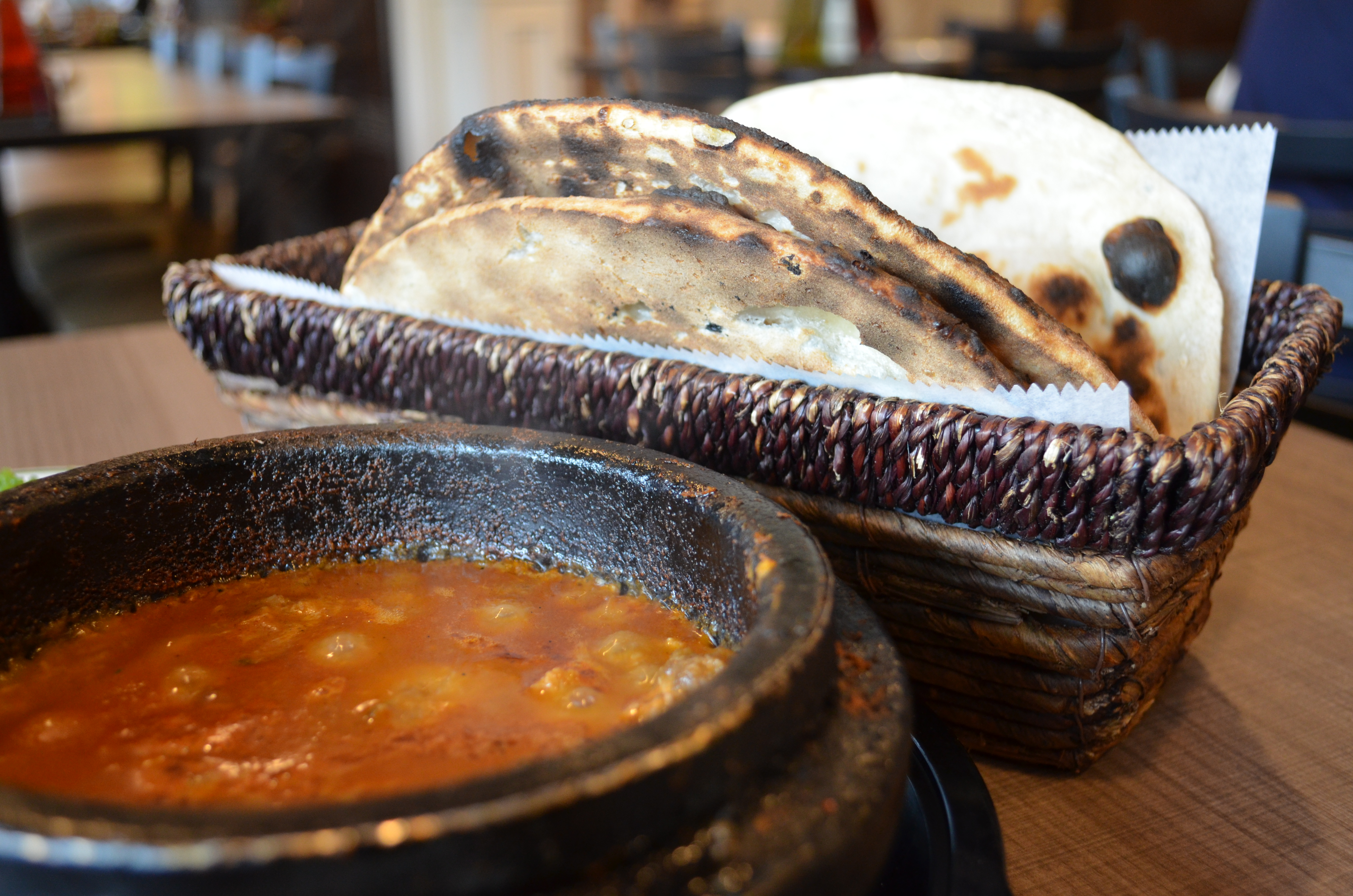 Close up photo of steaming clay pot of fahsah with pita bread.