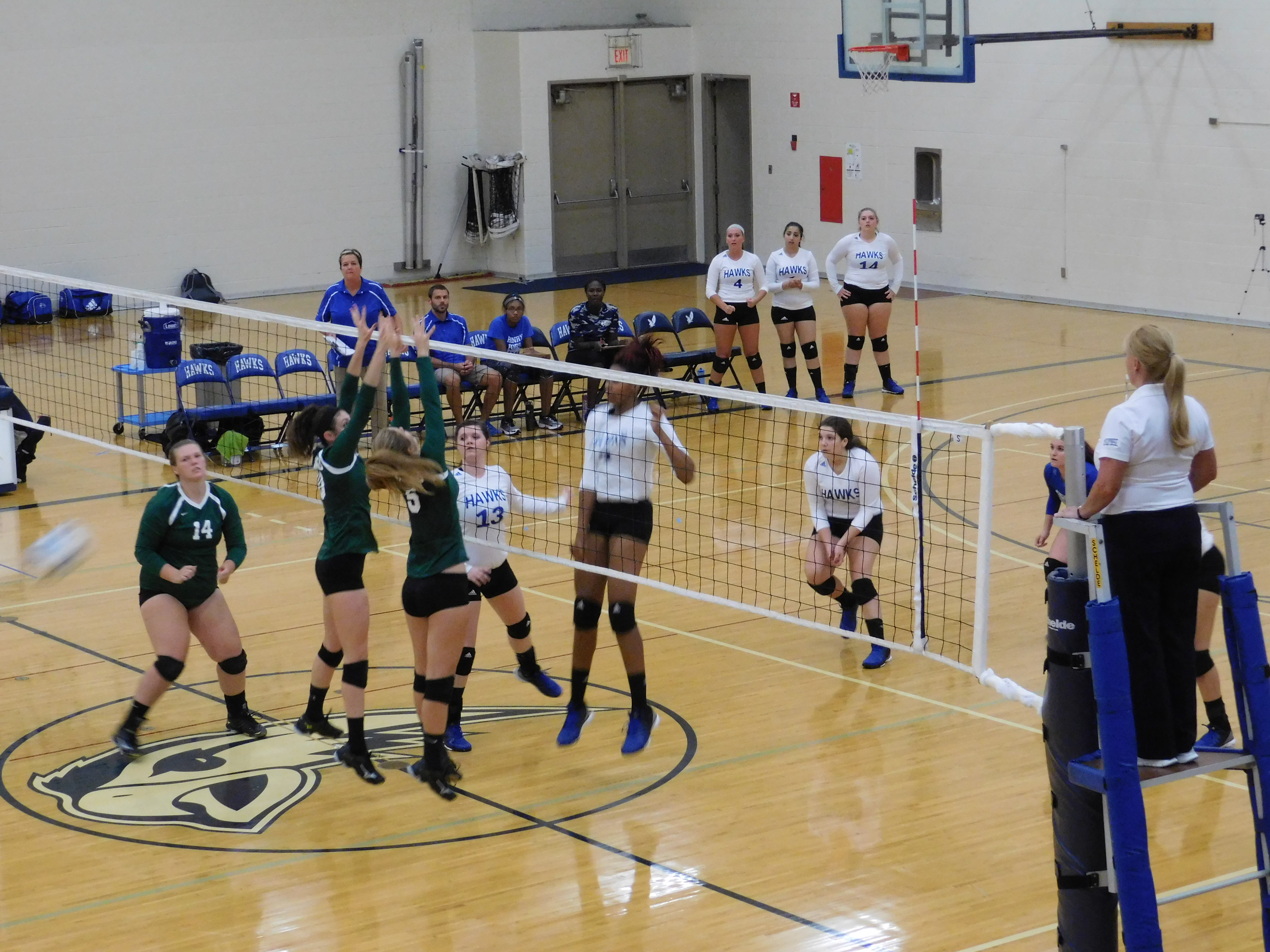 Hawks girls volleyball team at the net getting ready to block a spike.