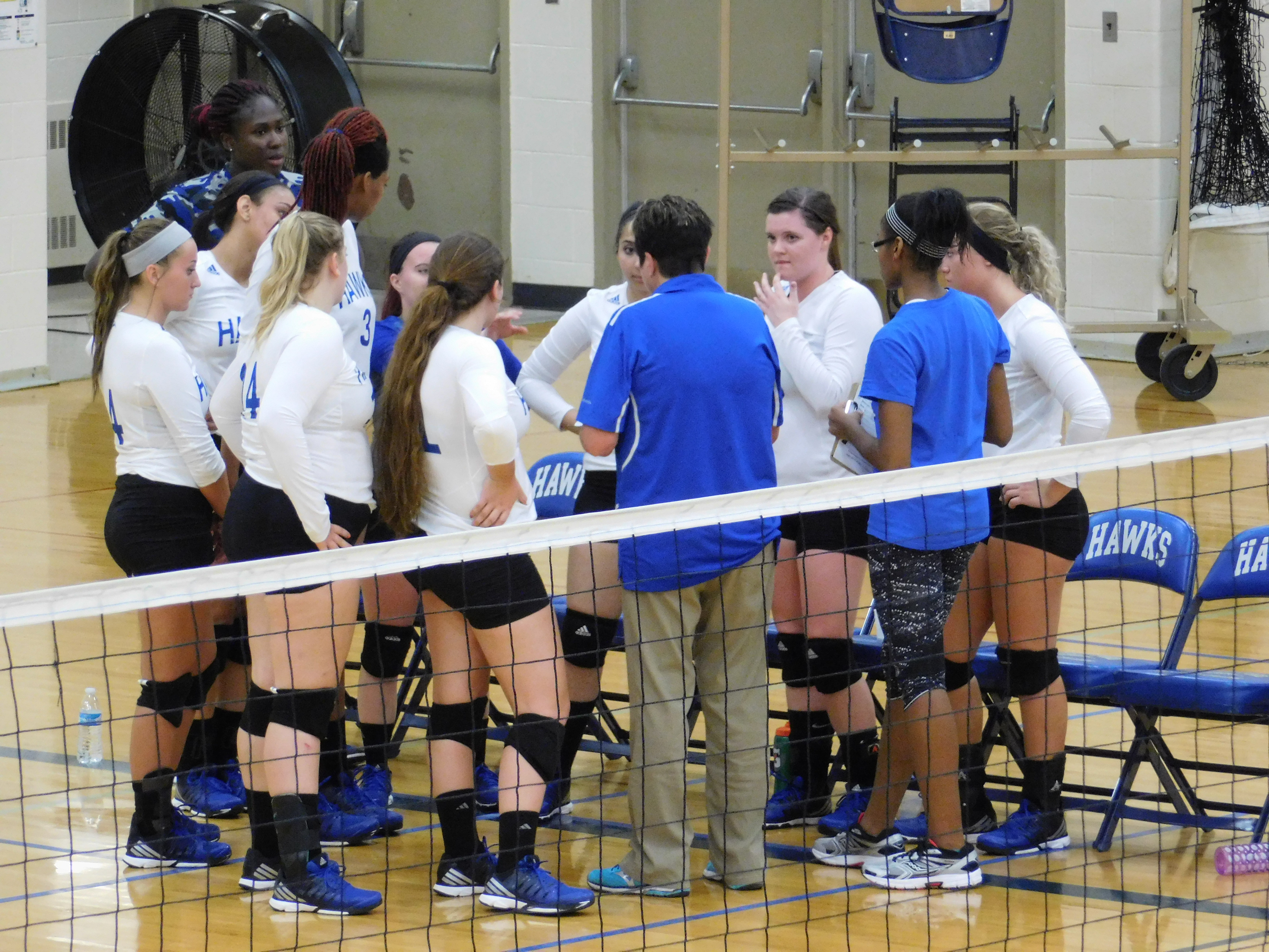 Hawks girls volleyball team huddled around the coach during a time out.
