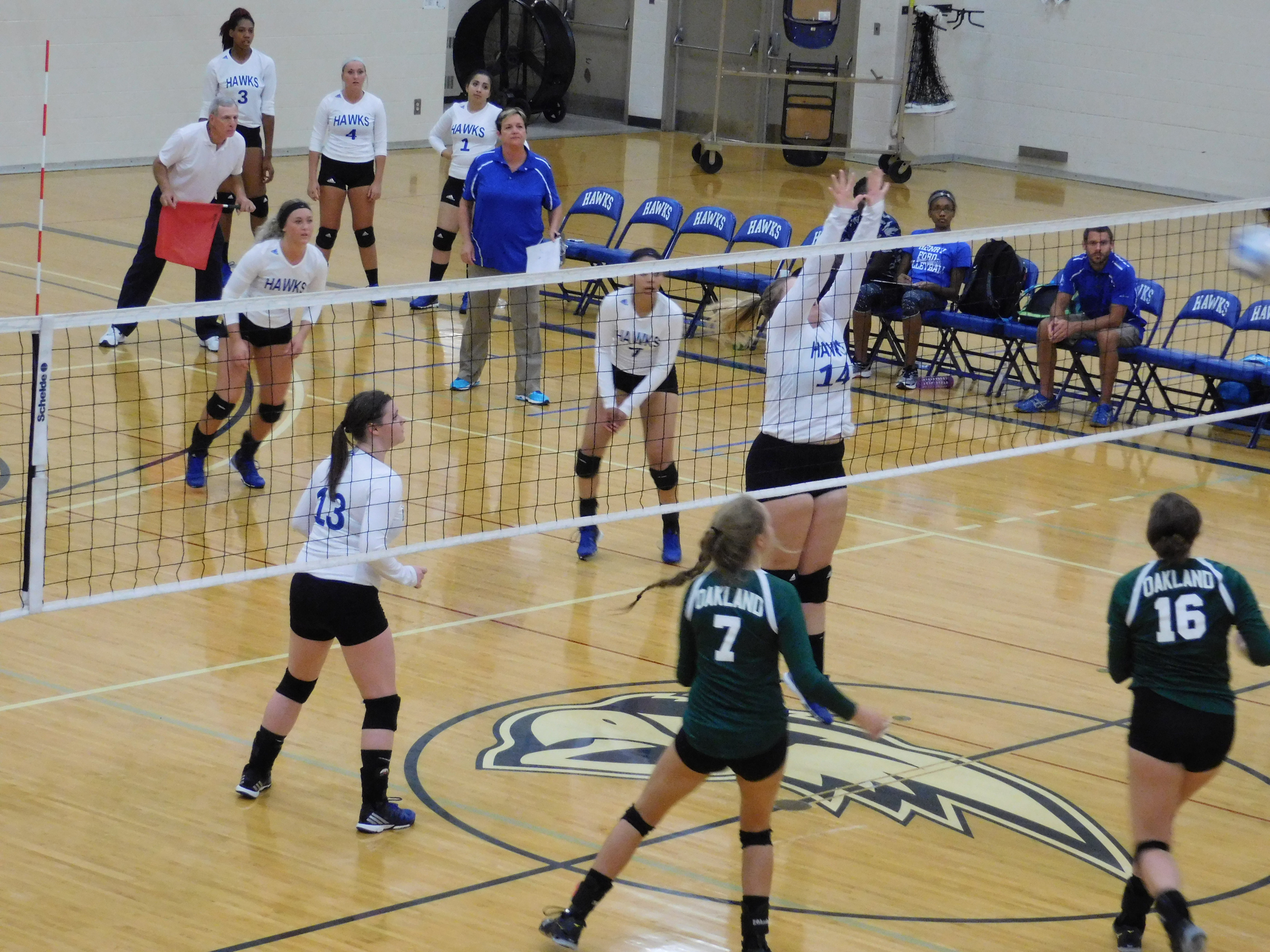 Hawks girls volleyball team blocking a shot from the opposing team.
