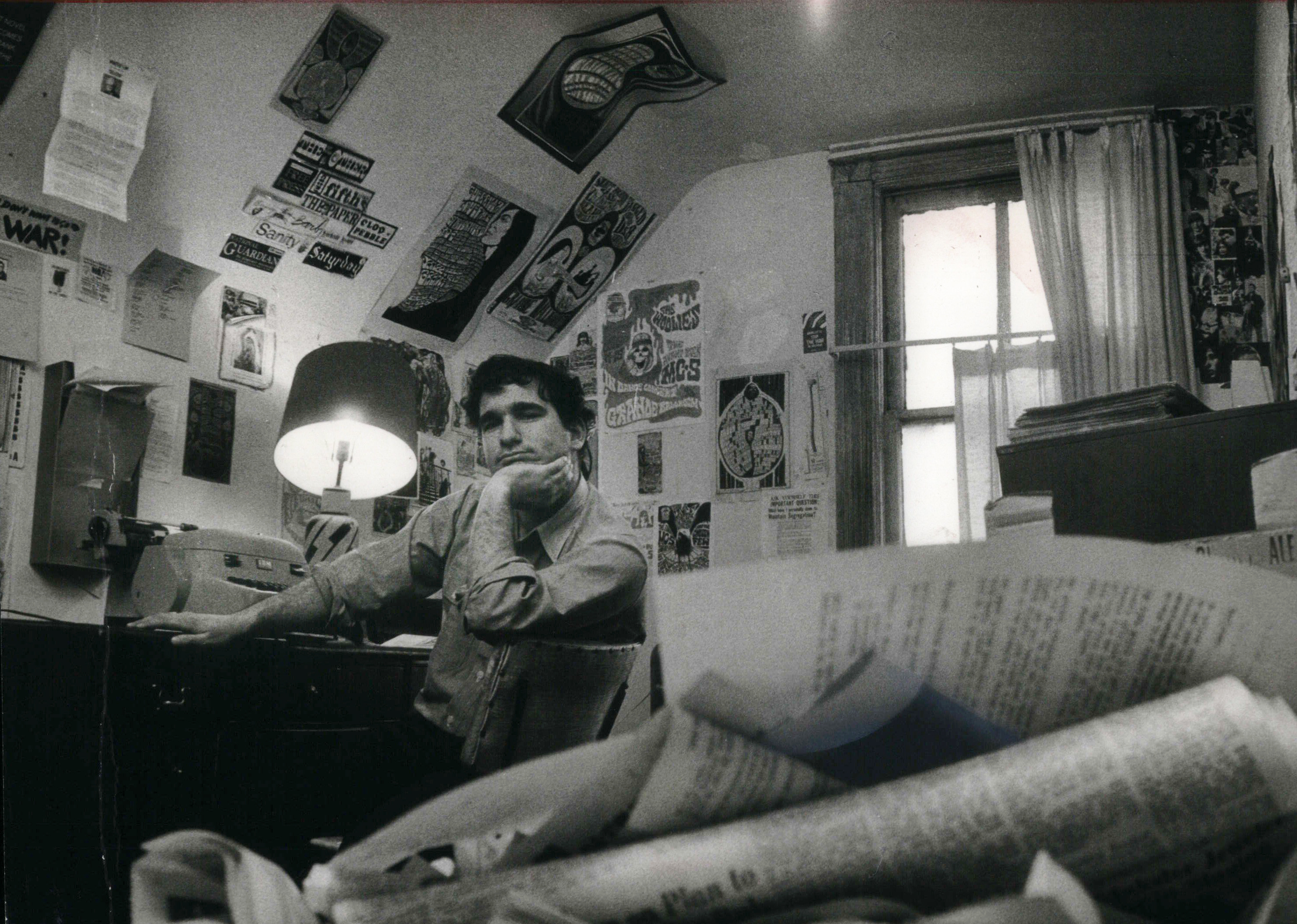 "Black and white photo of Harvey Ovshinsky as a young man in his apartment with front pages of ""The Fifth Estate"" on the wall."