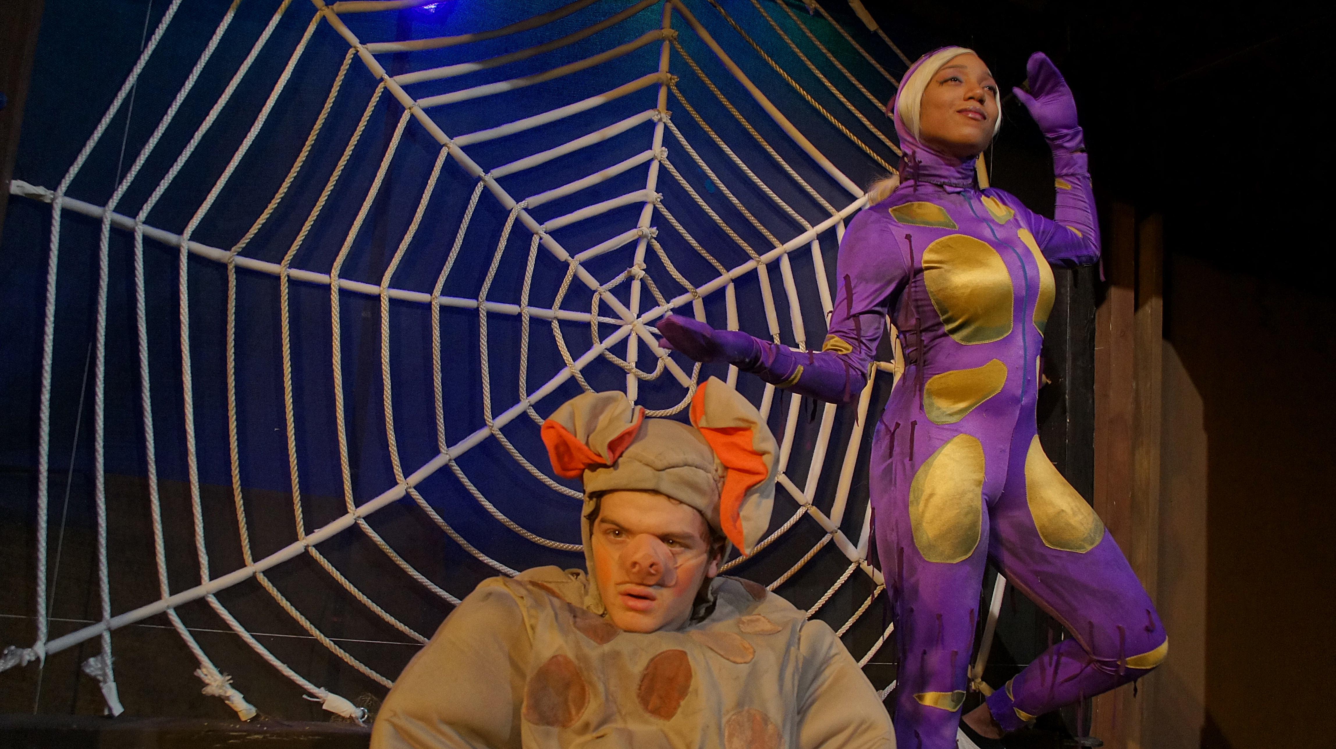 Photo of stage production of Charlotte's Web with large web and actor Dakota Nuttall in Wilbur the pig costume in front of actress Natasha Hawkins in Charlotte the spider costume.
