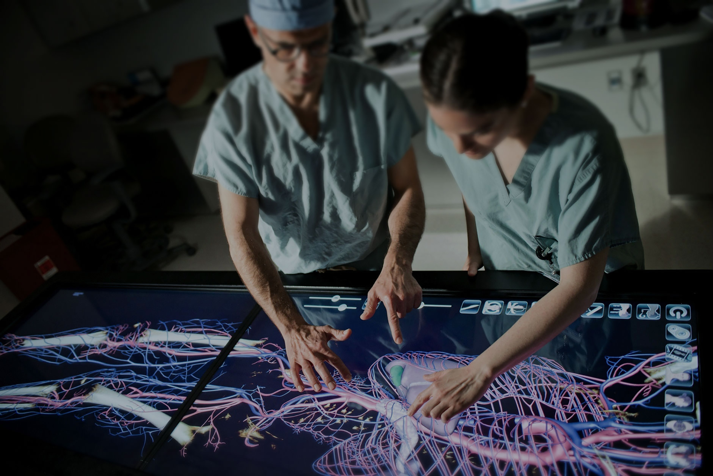 Two people of the medical crew examining the anatomy of human body using the anatomage table through a touchscreen that allows them to zoom in and move the 3D figure of the human body.