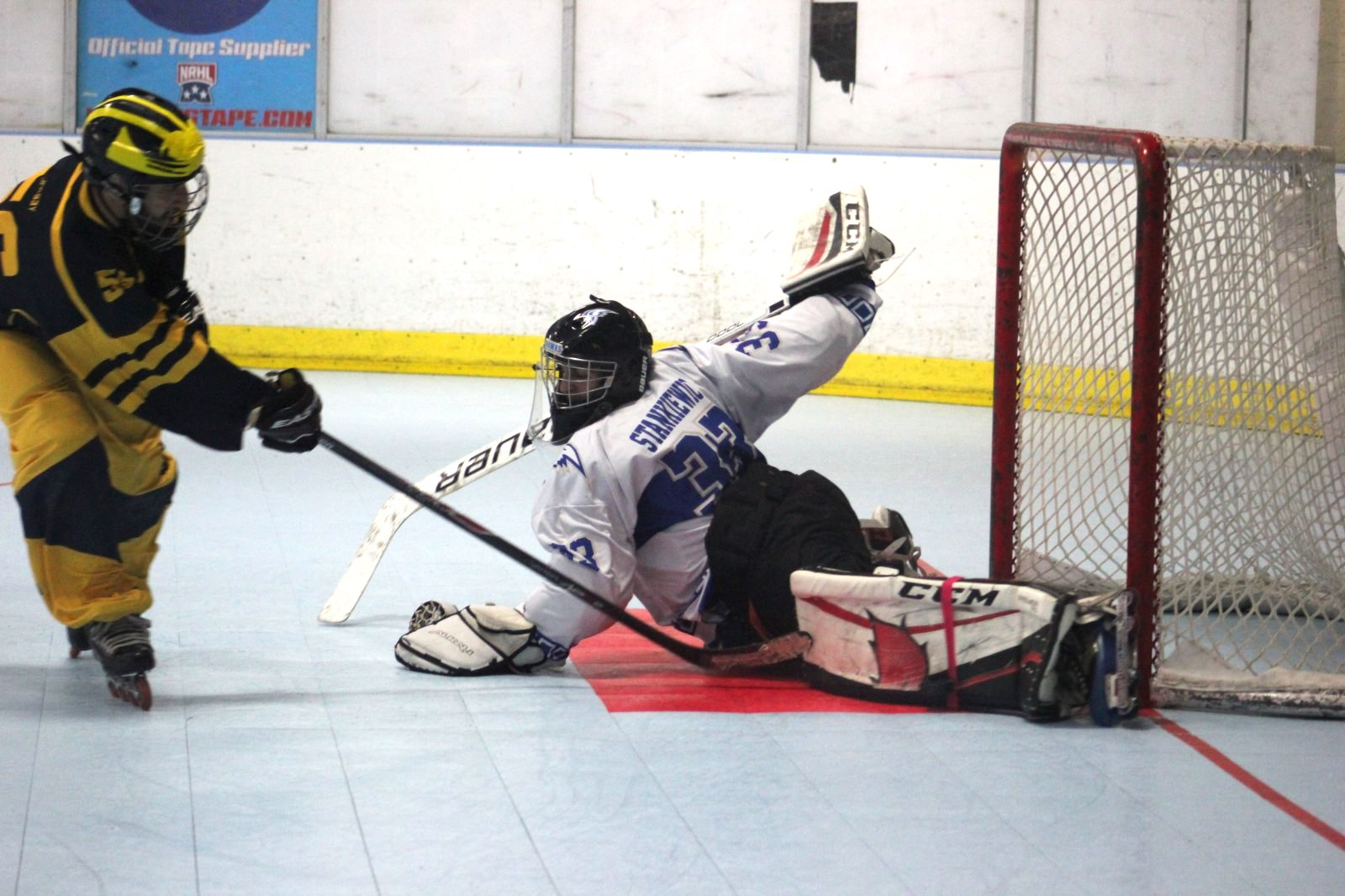 Goalie doing splits to stop goal.