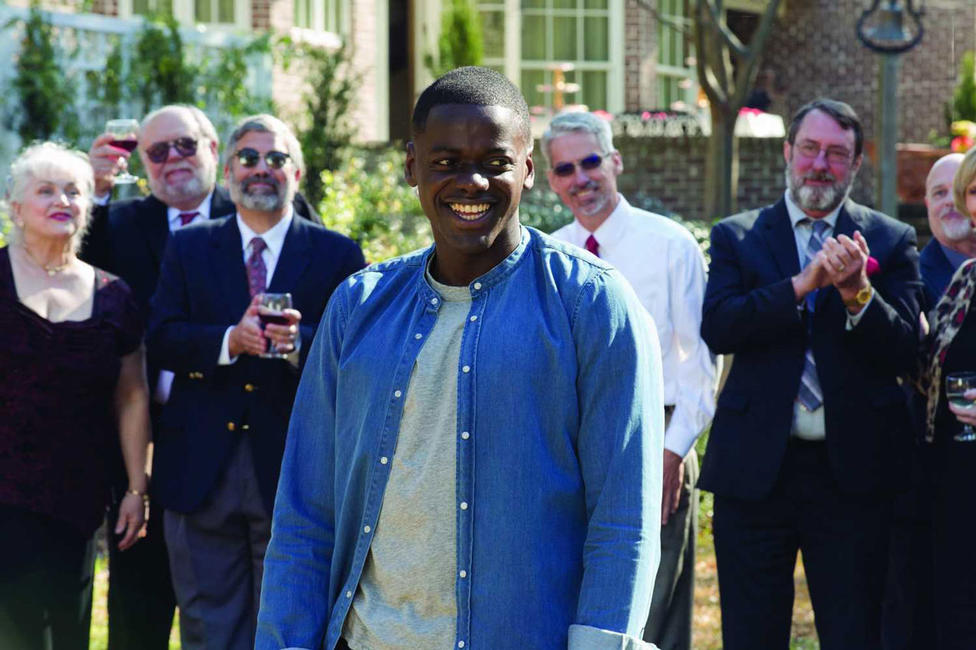 "Film scene from ""Get Out"" with the main character at an outdoor dinner party."