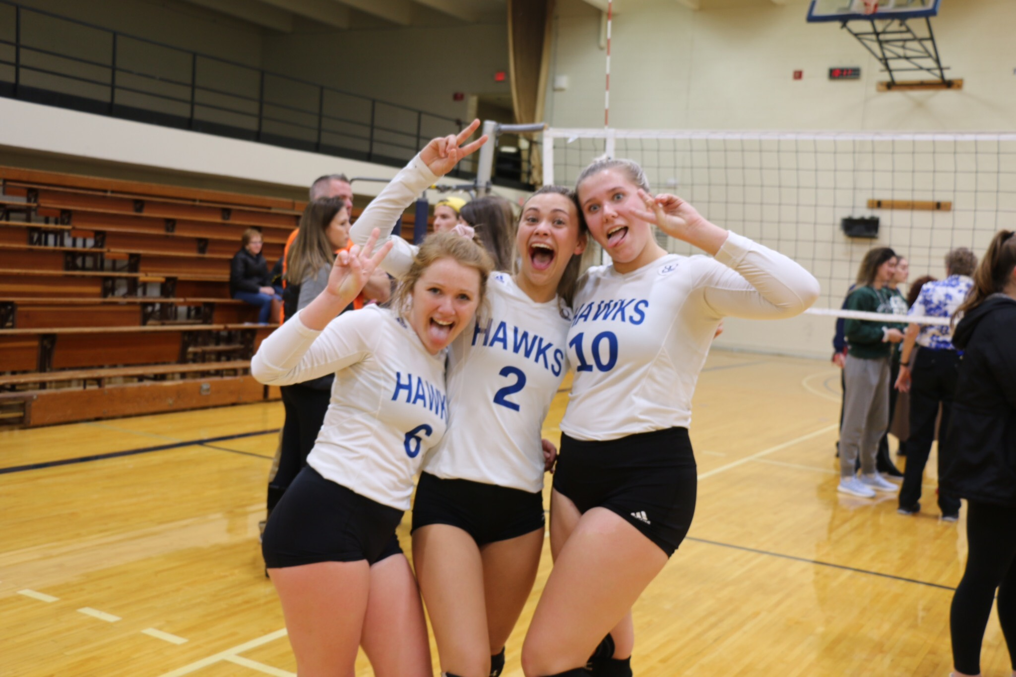 Photograph of three HFC Volleyball players: Hannah Sullivan, Emily Schroeder, and Katelyn Pinkowski.