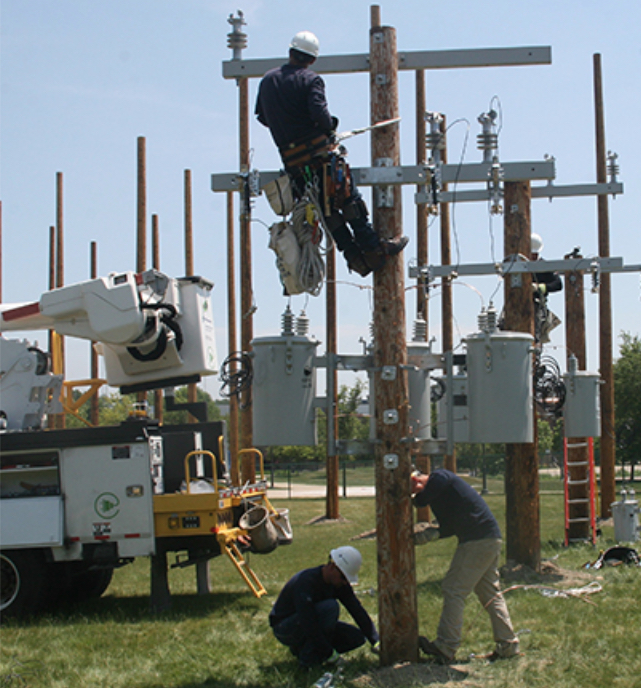 Photo shows student electricians working on an electrical pole