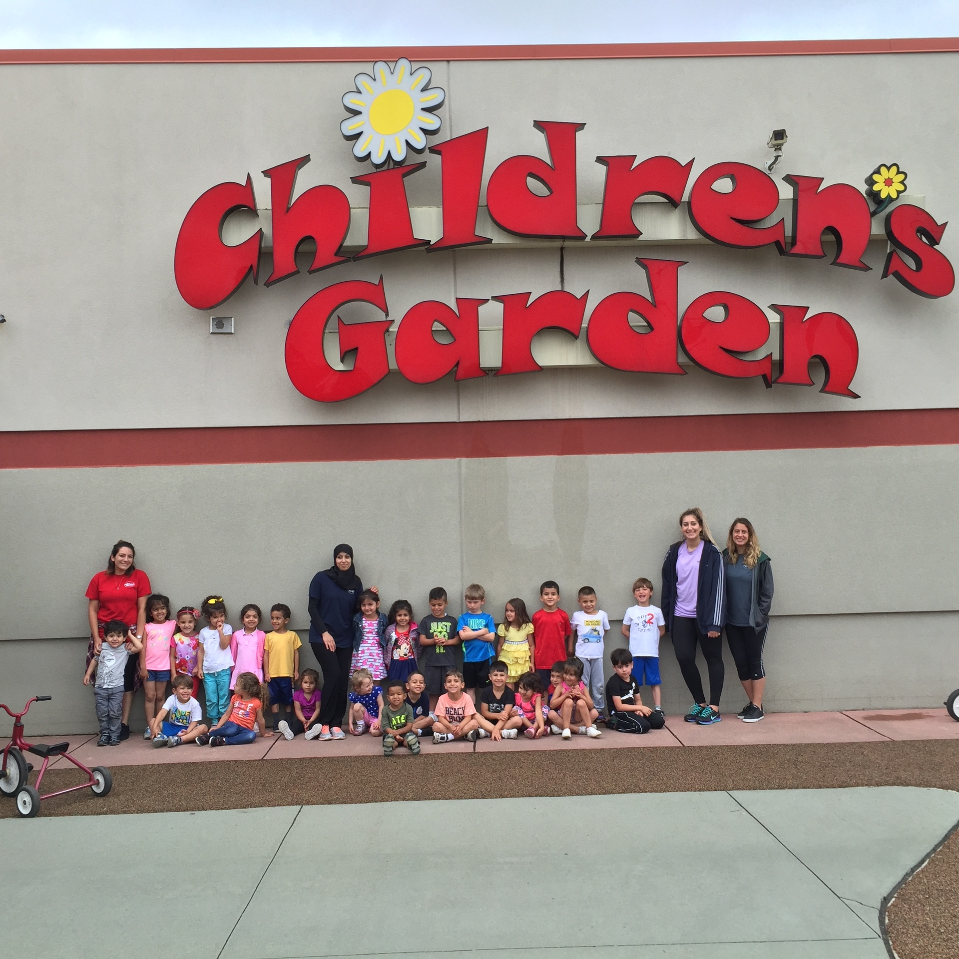 Image of a group of people and children standing outside of Children's Garden daycare