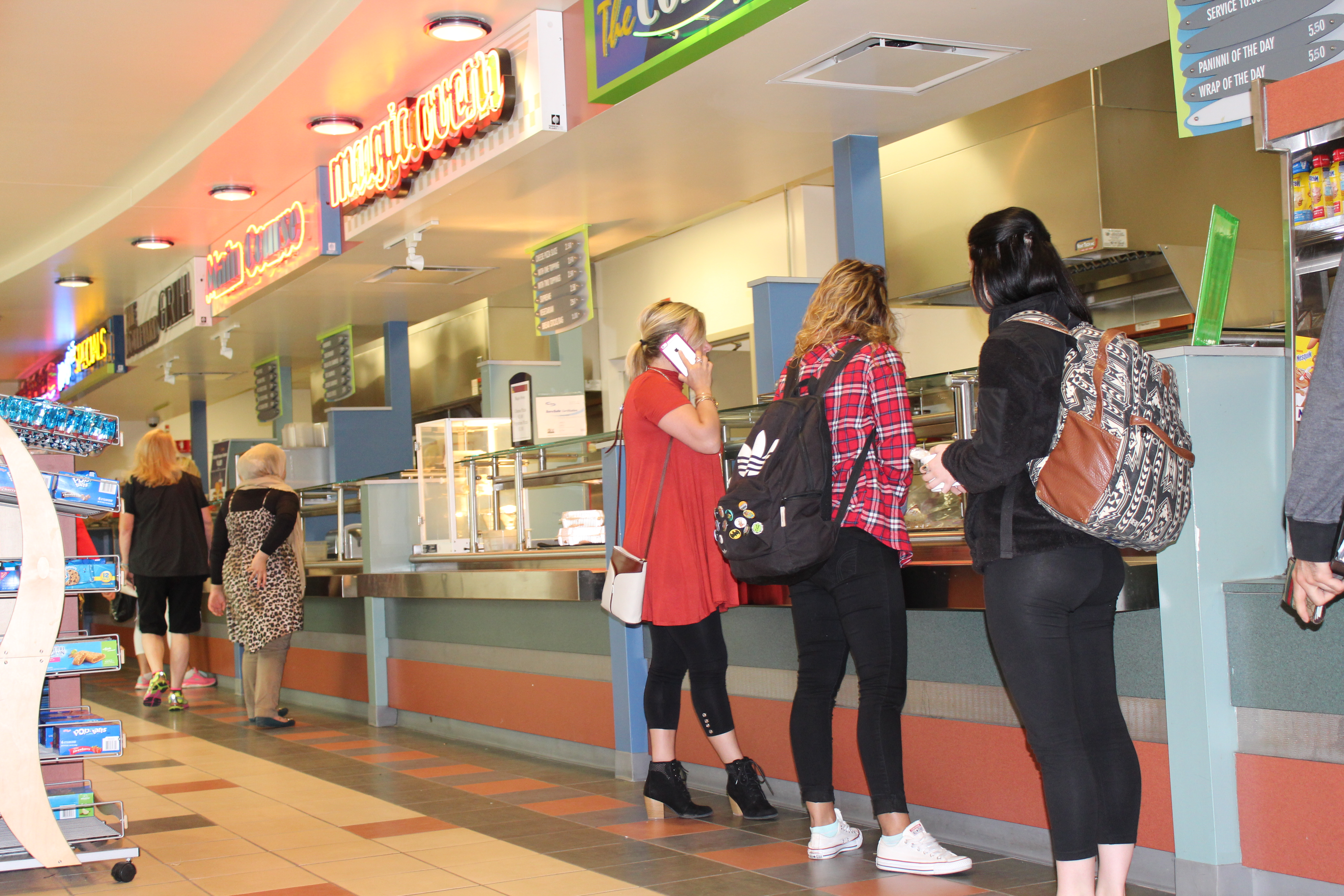 Students waiting for food at the cafeteria serving area with neon signs above them indicating different food options.