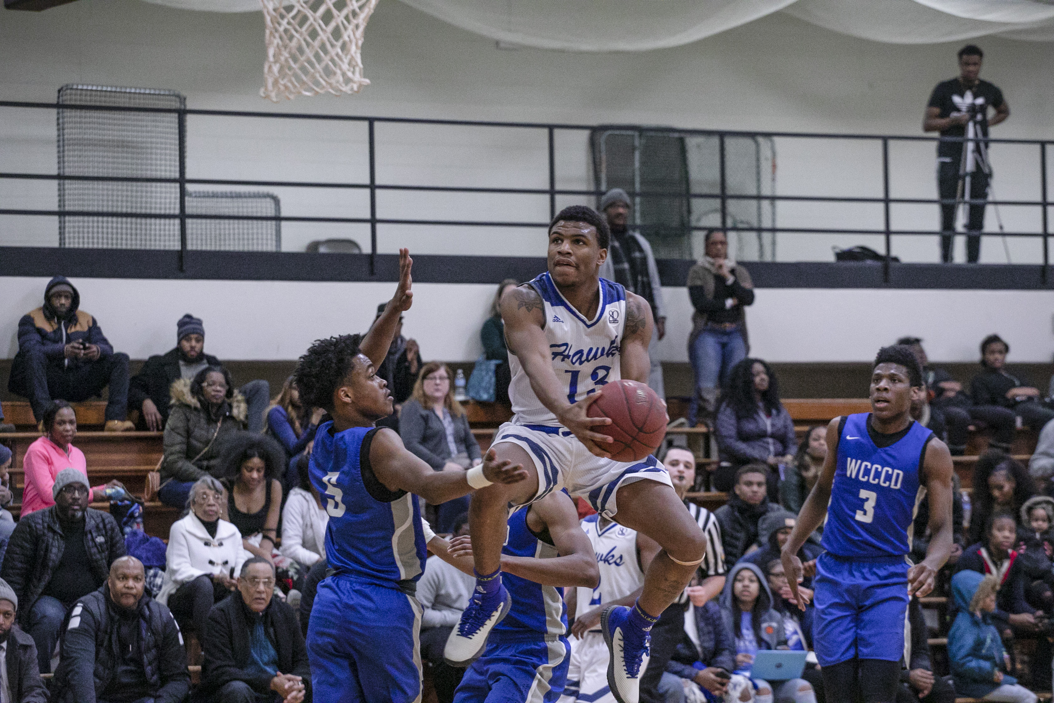HFC's Luster Johnson driving to the hoop for a reverse layup with a defender on him