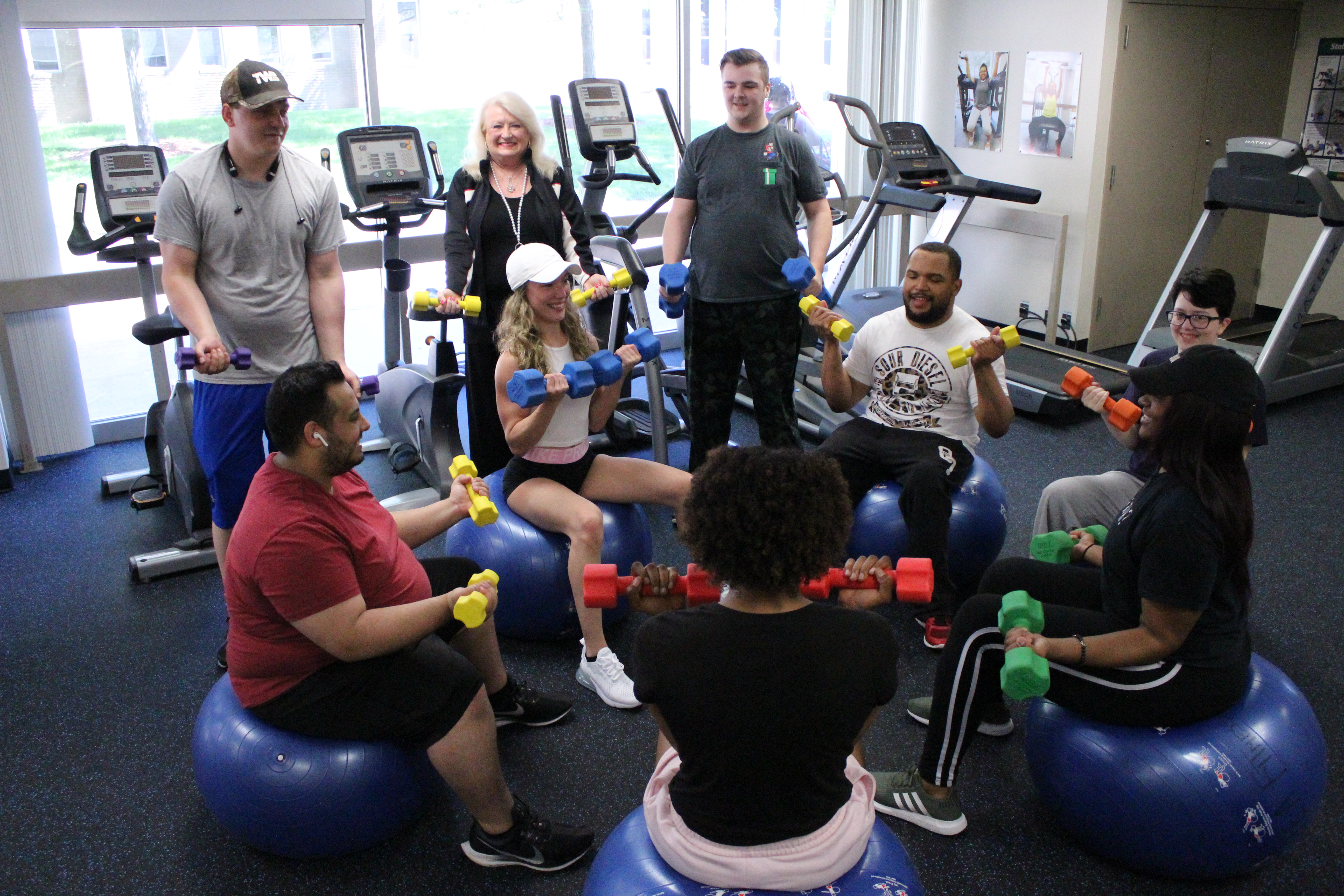 Image of a fitness class using dumbbells and exercise balls