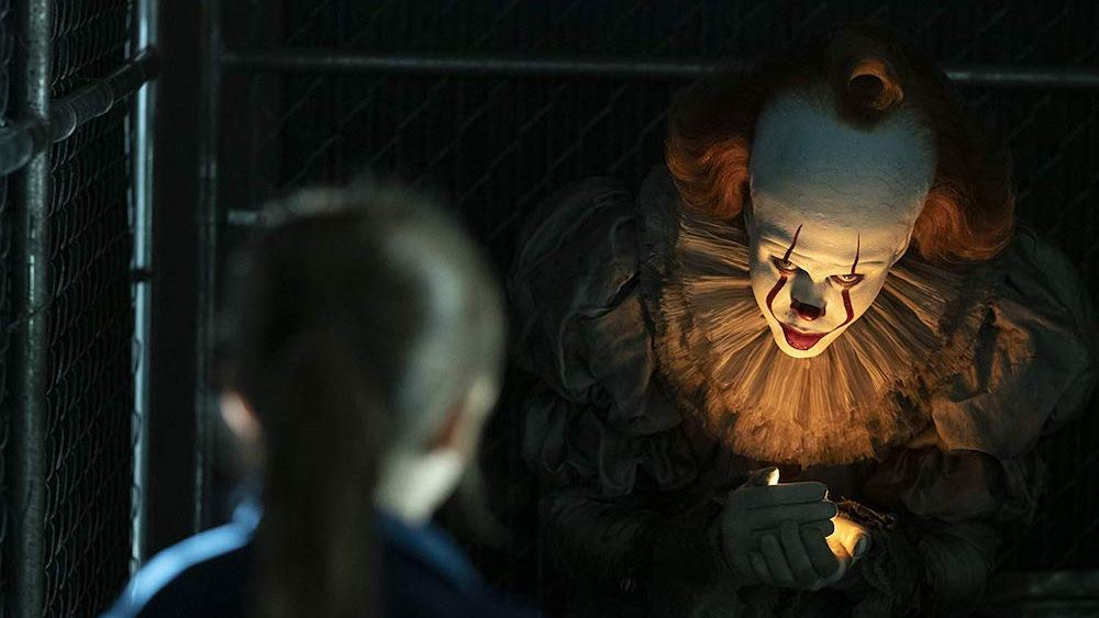 """Image still from """"It"""" showing Pennywise the clown enticing a child"""