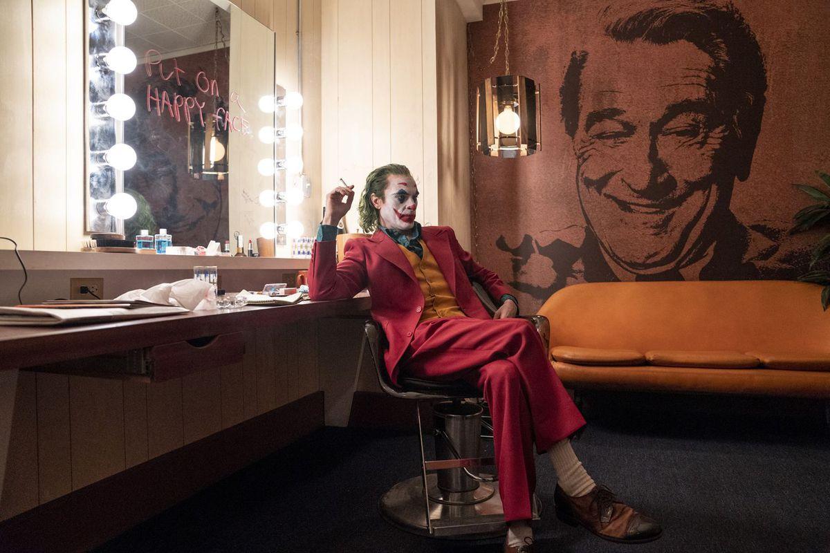 "Photo shows Joaquin Phoenix as ""Joker"" sitting in a dressing room near a mural of Robert De Niro"