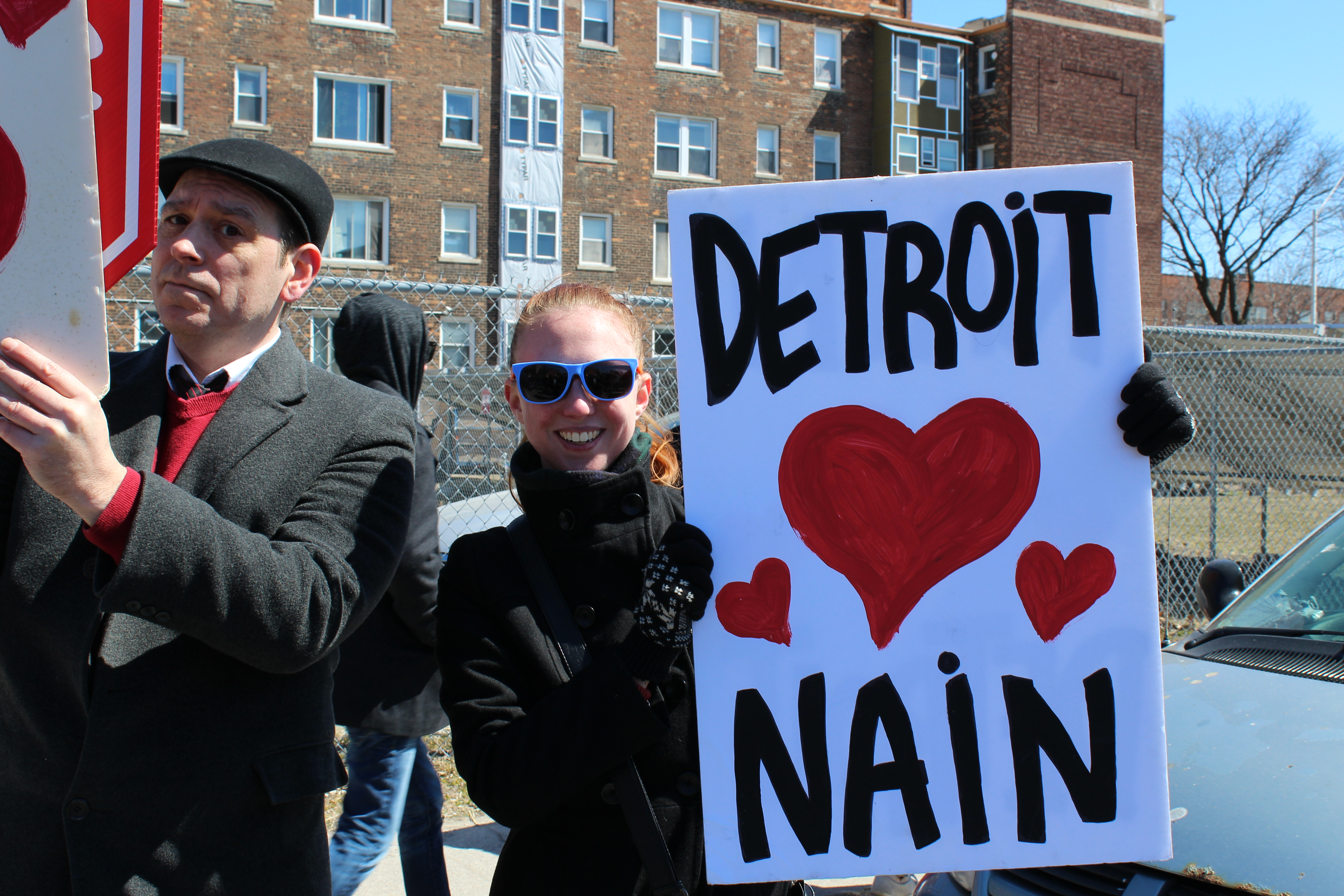 A man marching with the mache du nain holding a sign that says Detroit heart Nain