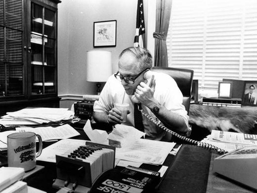 Black-and-white photo of U.S. Representative John Dingell on the phone