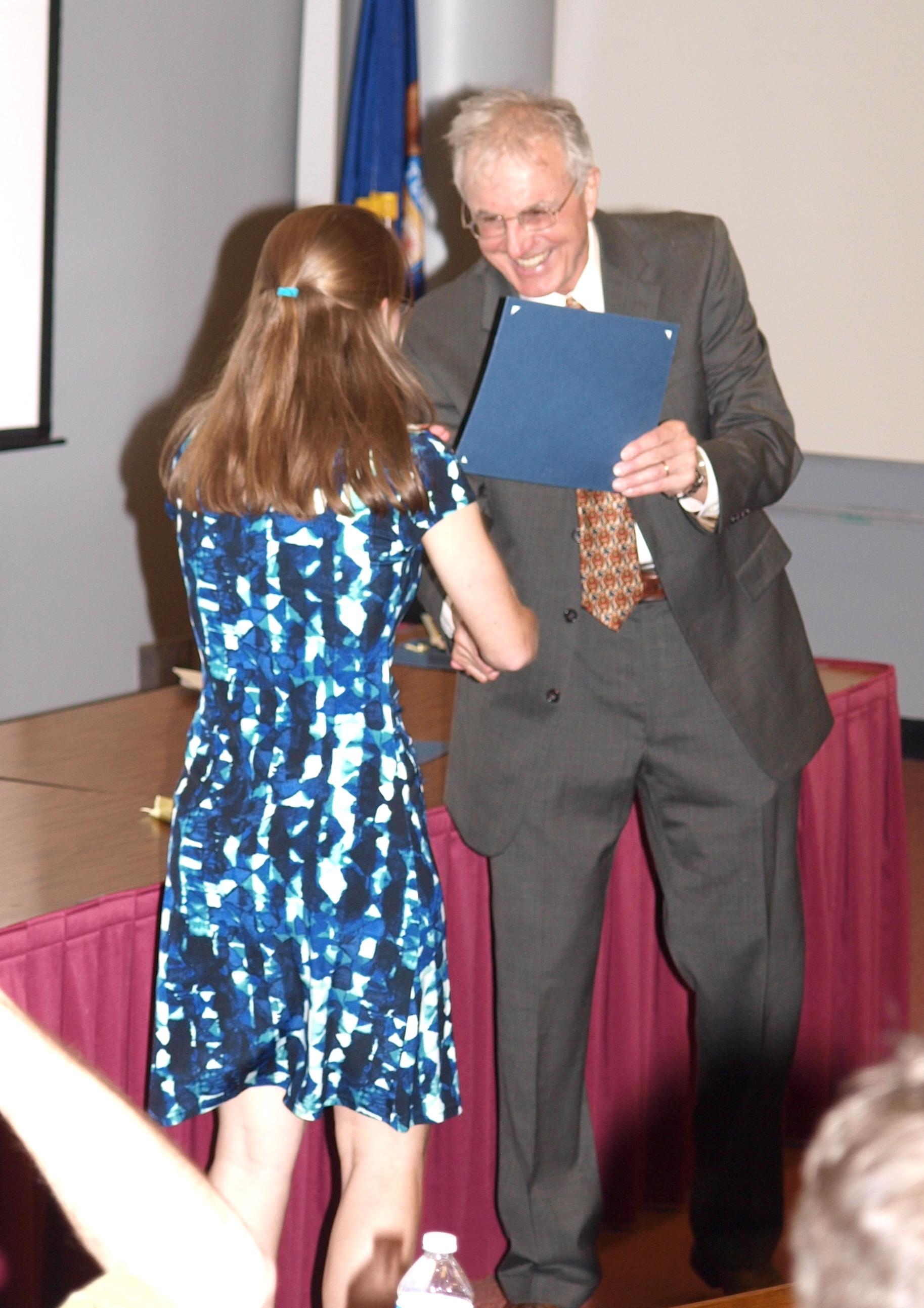 Dr. Michael Daher handing an award to a student