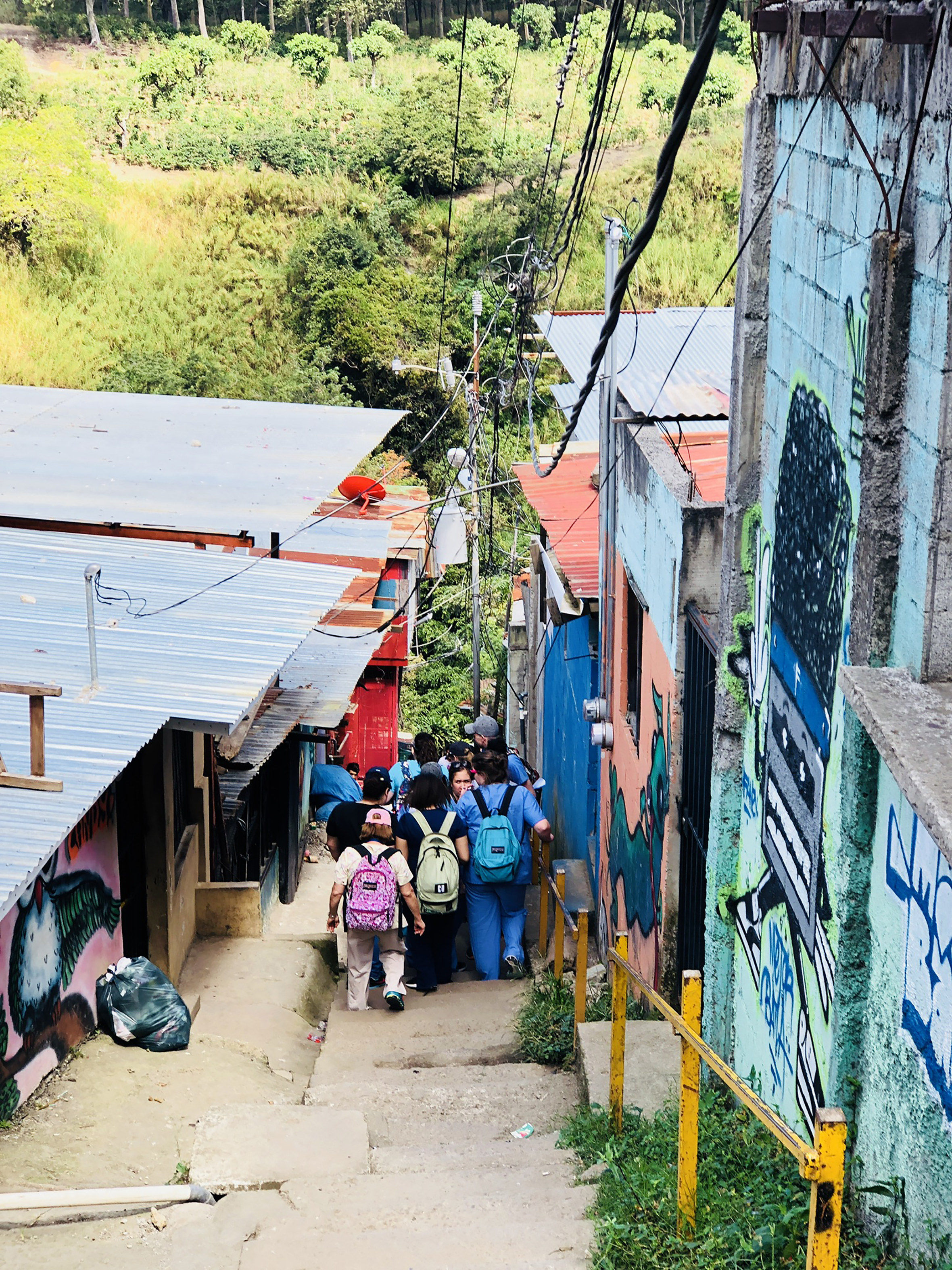 A picture of students walking in a narrow way between houses in Costa Rica