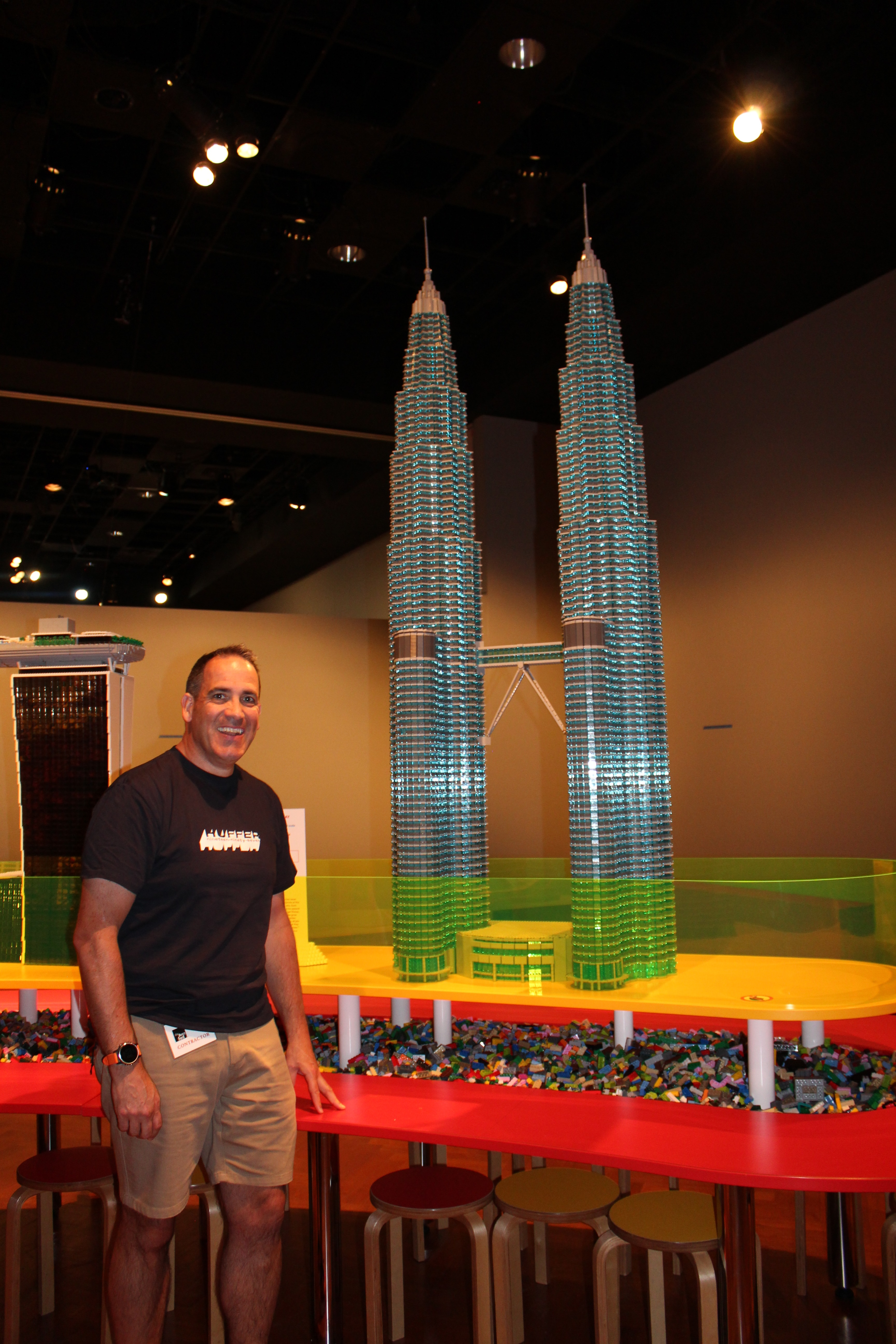Photo shows Ryan McNaught standing next to a lego replica of the Petronas Towers