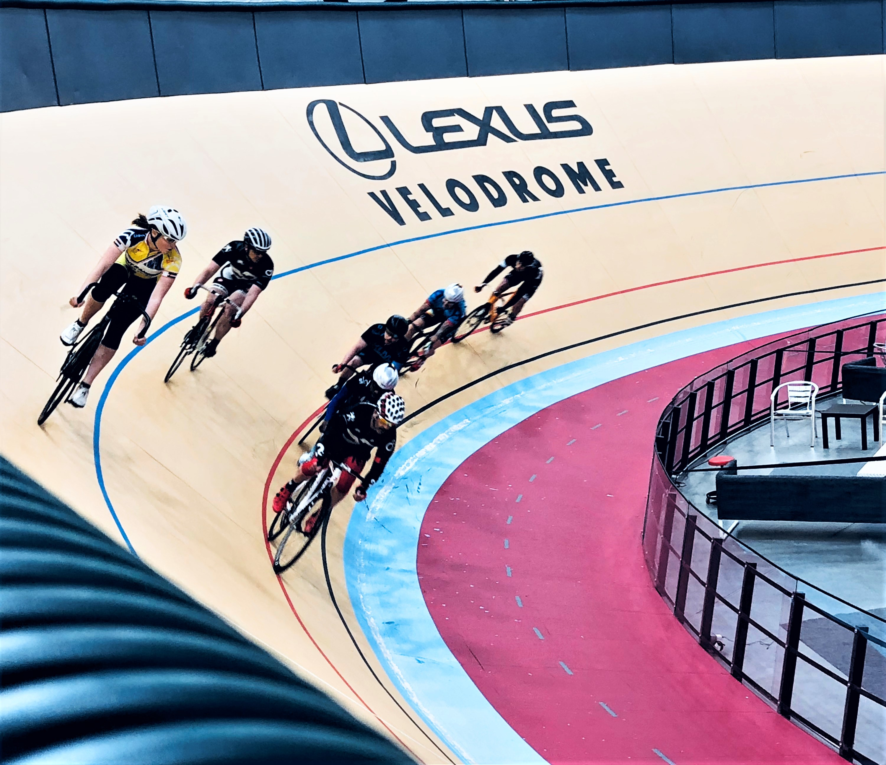 Seven cyclers racing at the Lexus Velodrome cycling track.