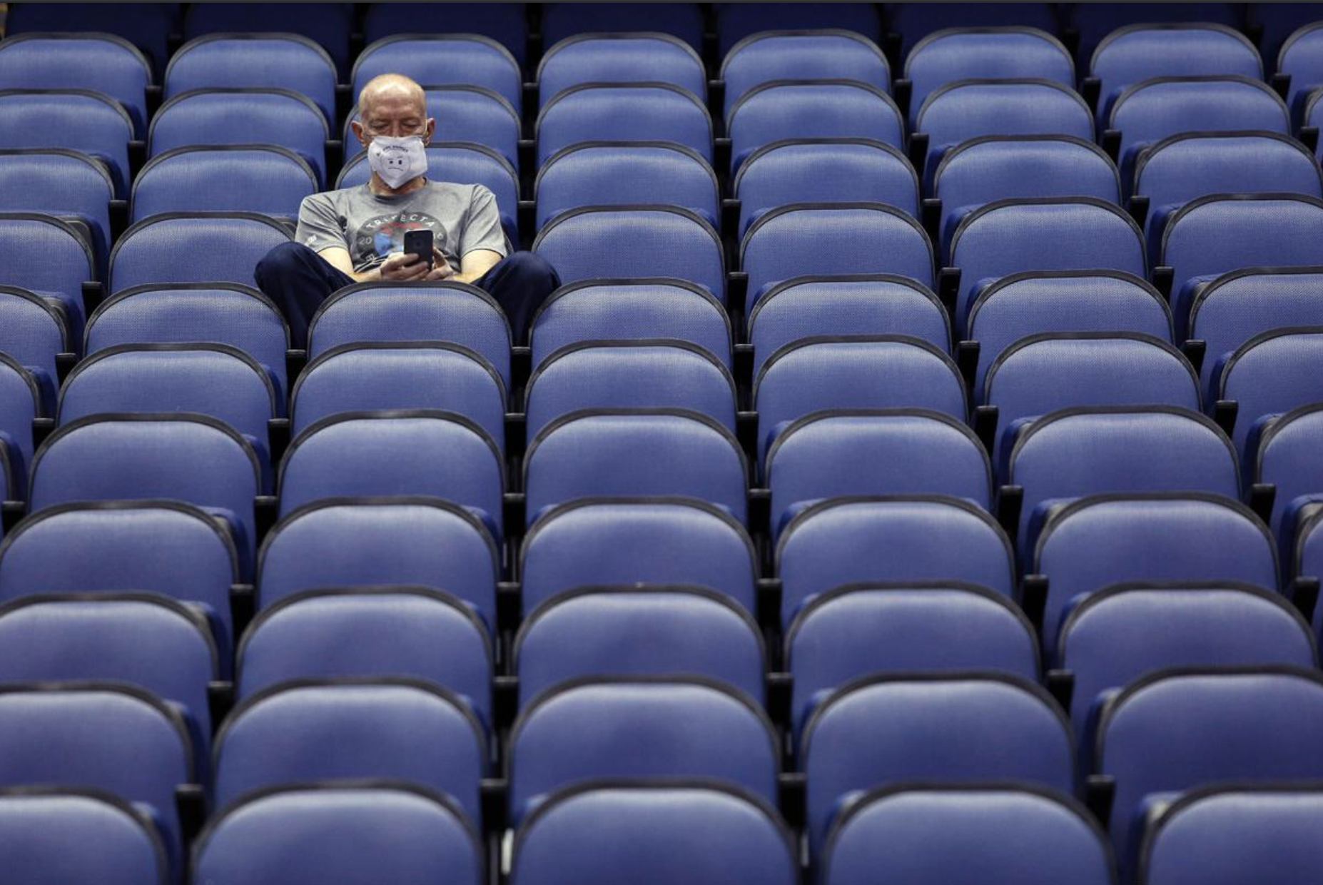 Photo shows a man wearing a surgical mask sitting alone in an empty stadium