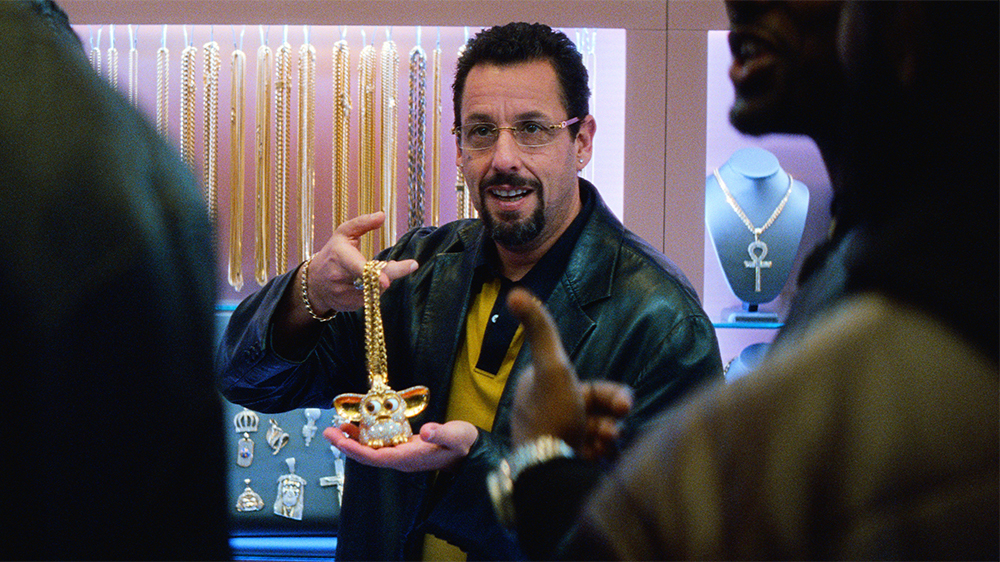 """Still image from """"Uncut Gems"""" showing Adam Sandler holding a Furby gold chain"""