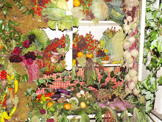 A cabinet overflows with fruit, and vegetables, leaves and moss. It has been arranged in an artful manner.