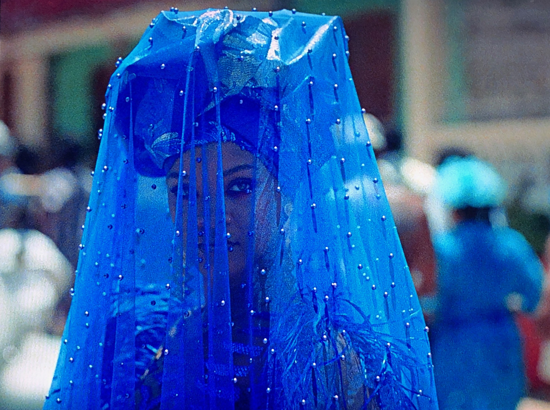 "Photo of Rihanna in scene from ""Guava Island"" as Kofi dressed in blue veil"