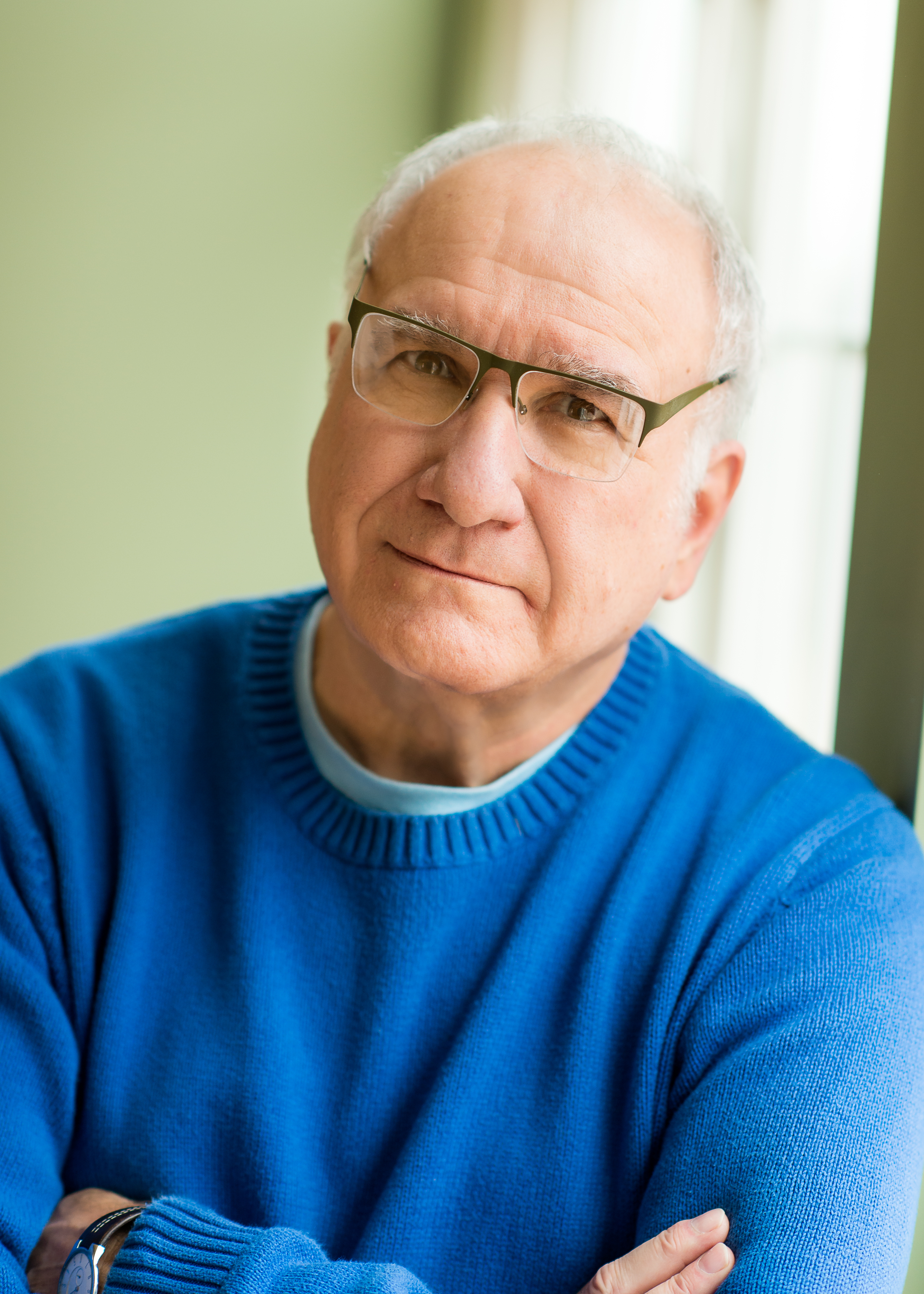 Profile photo of Harvey Ovshinsky and how he looks today with short white hair, wire-rim glasses, wearing a crew neck sky blue sweater.