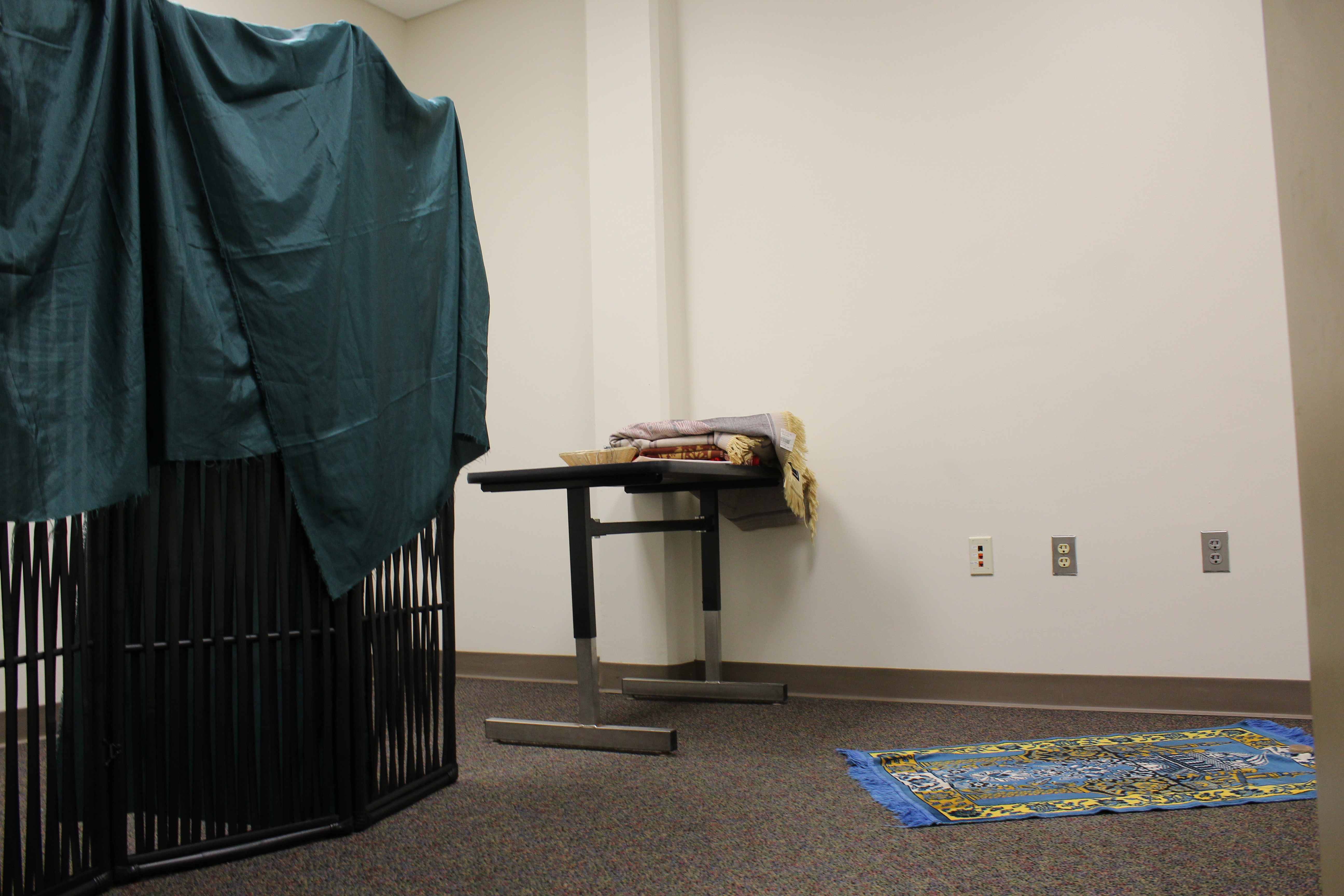 A simple room with a room divider draped with fabric on the left. A small table holds prayer mats and one is rolled out on the floor.