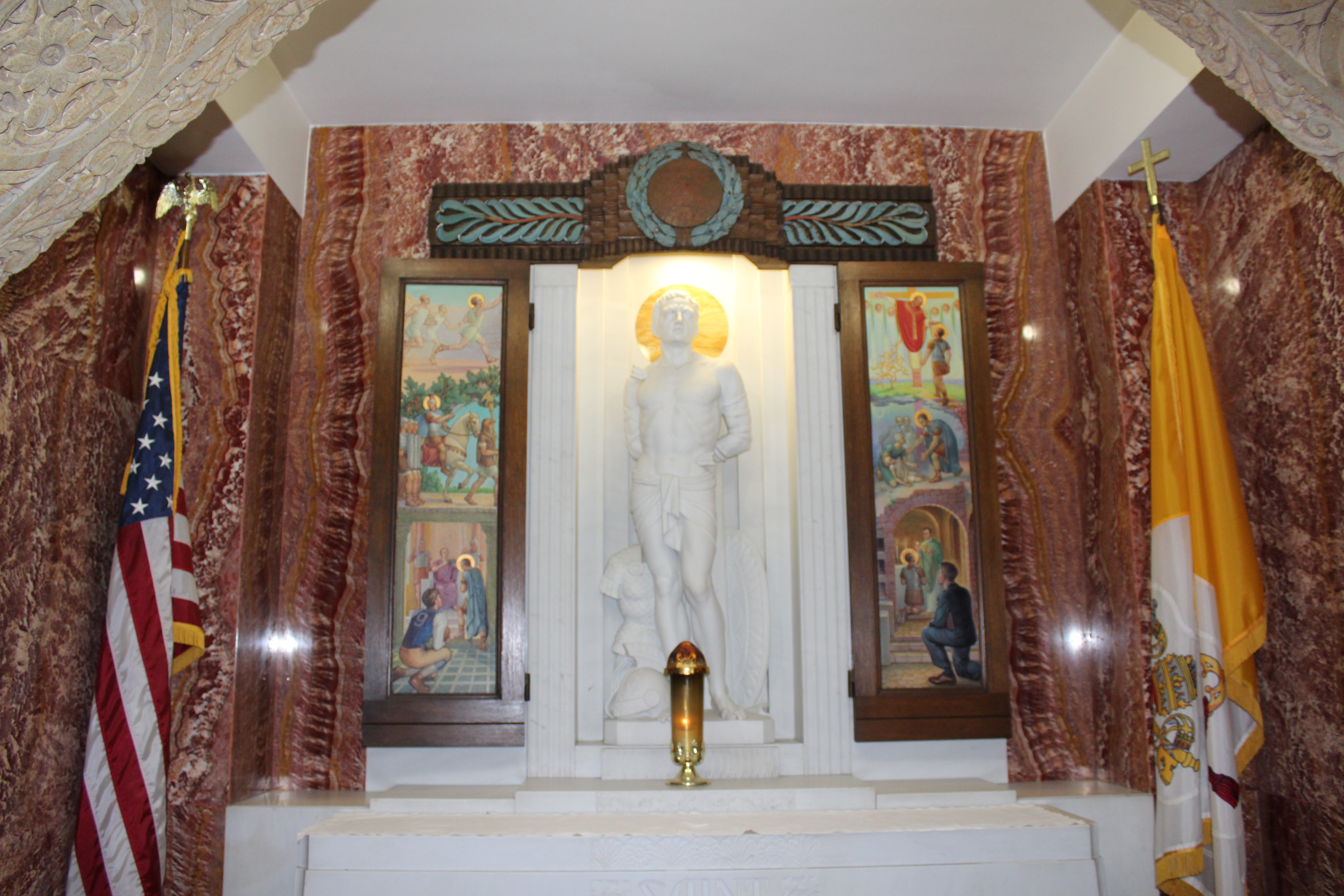 A marble statue of a saint is flanked by paintings of people.