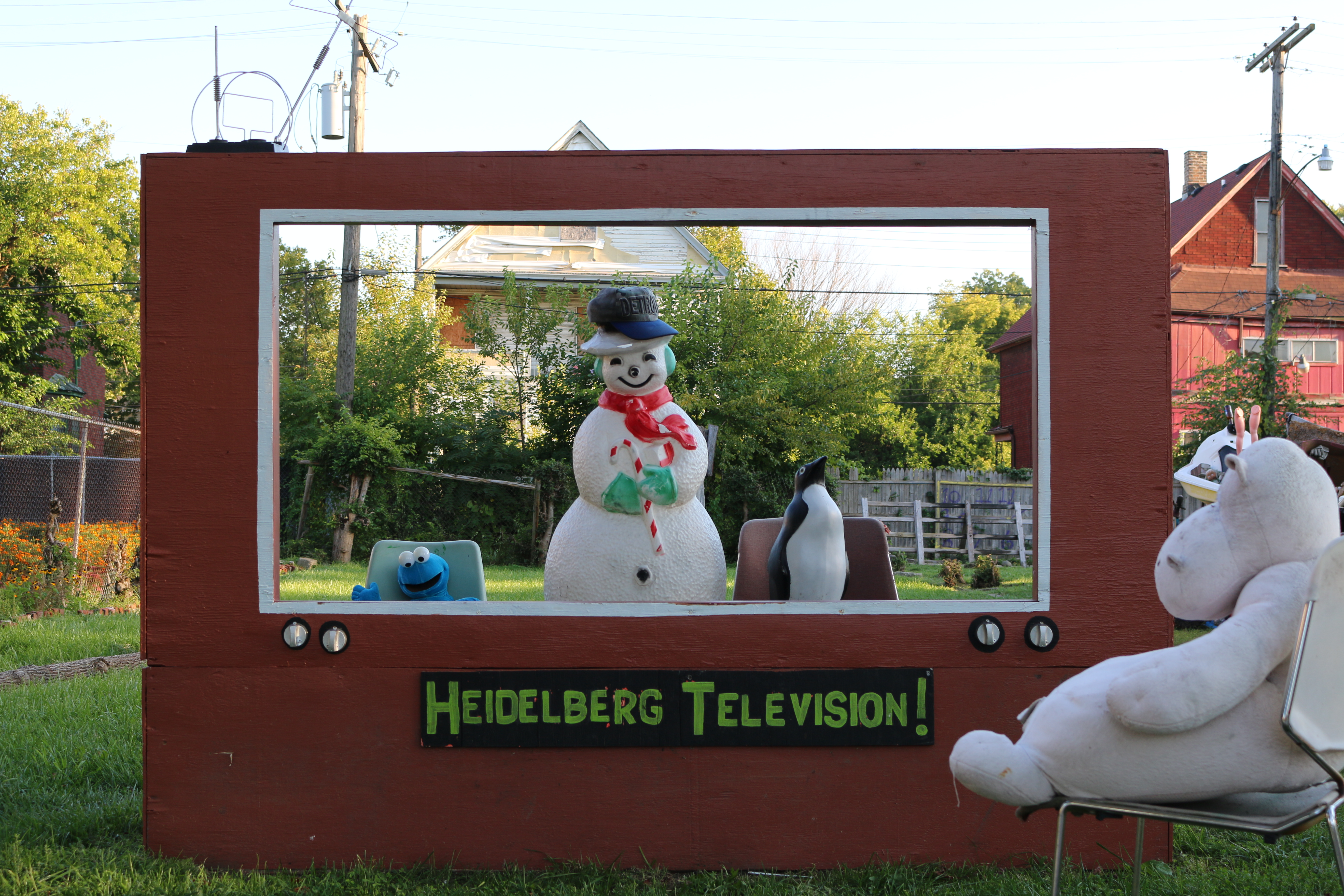 White snowman toy inside read wooden frame with stuffed hippo watching and blocked letters saying Heidelberg Television.