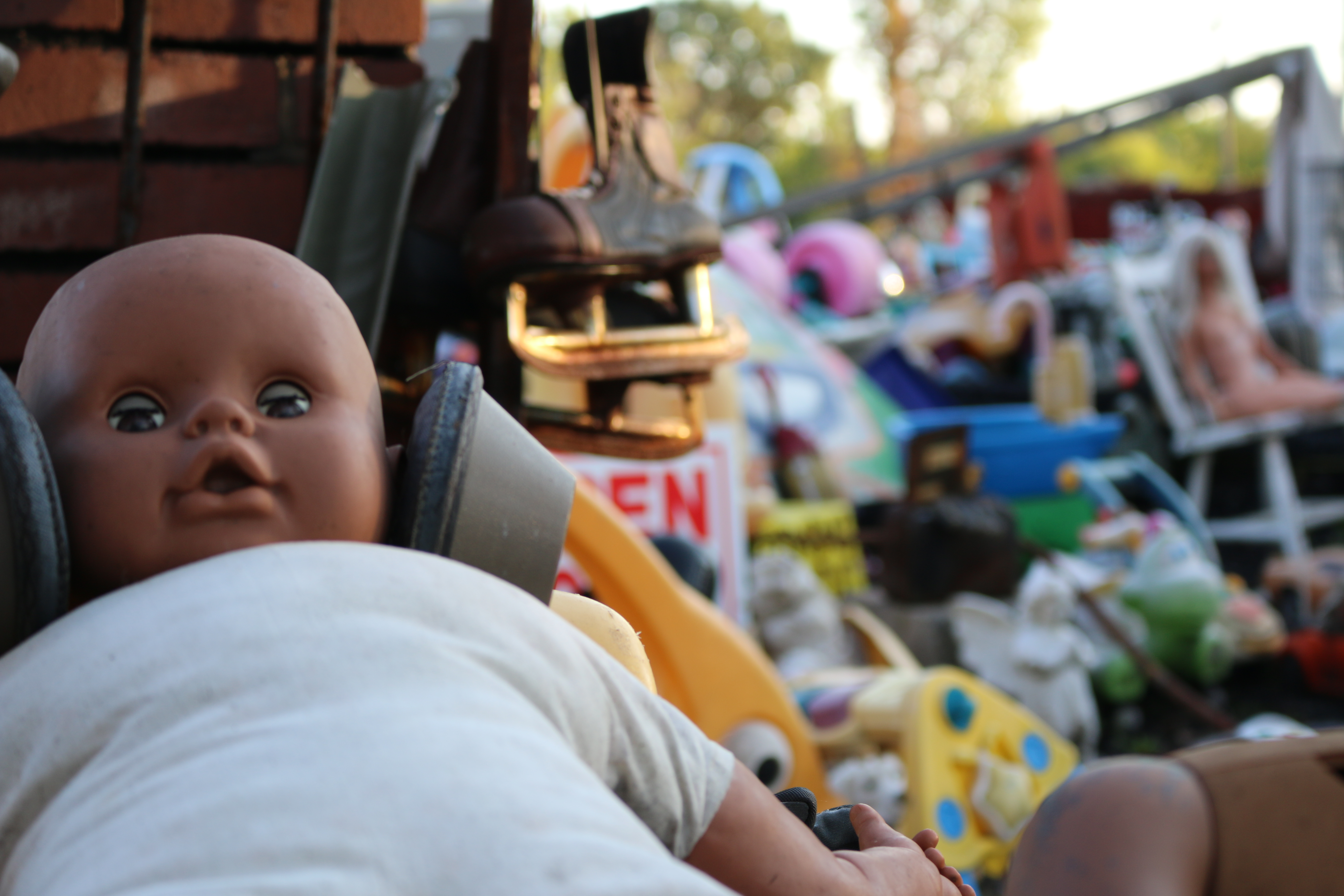 Close up of baby doll with colorful thrown away toys blurred in background.