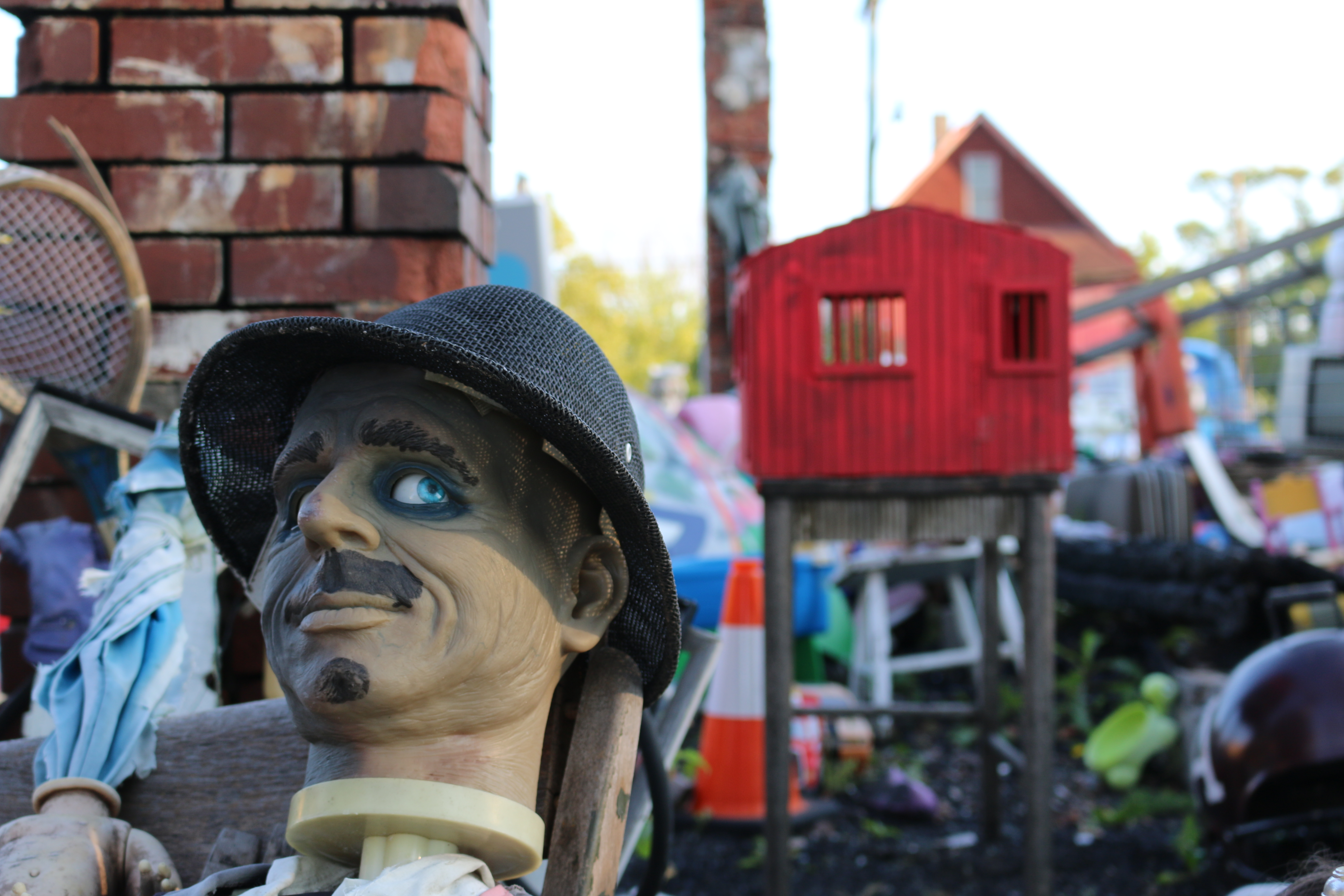 Close up of rubber head with blue eyeball and wool fedora; red shack on stilts blurred in background.