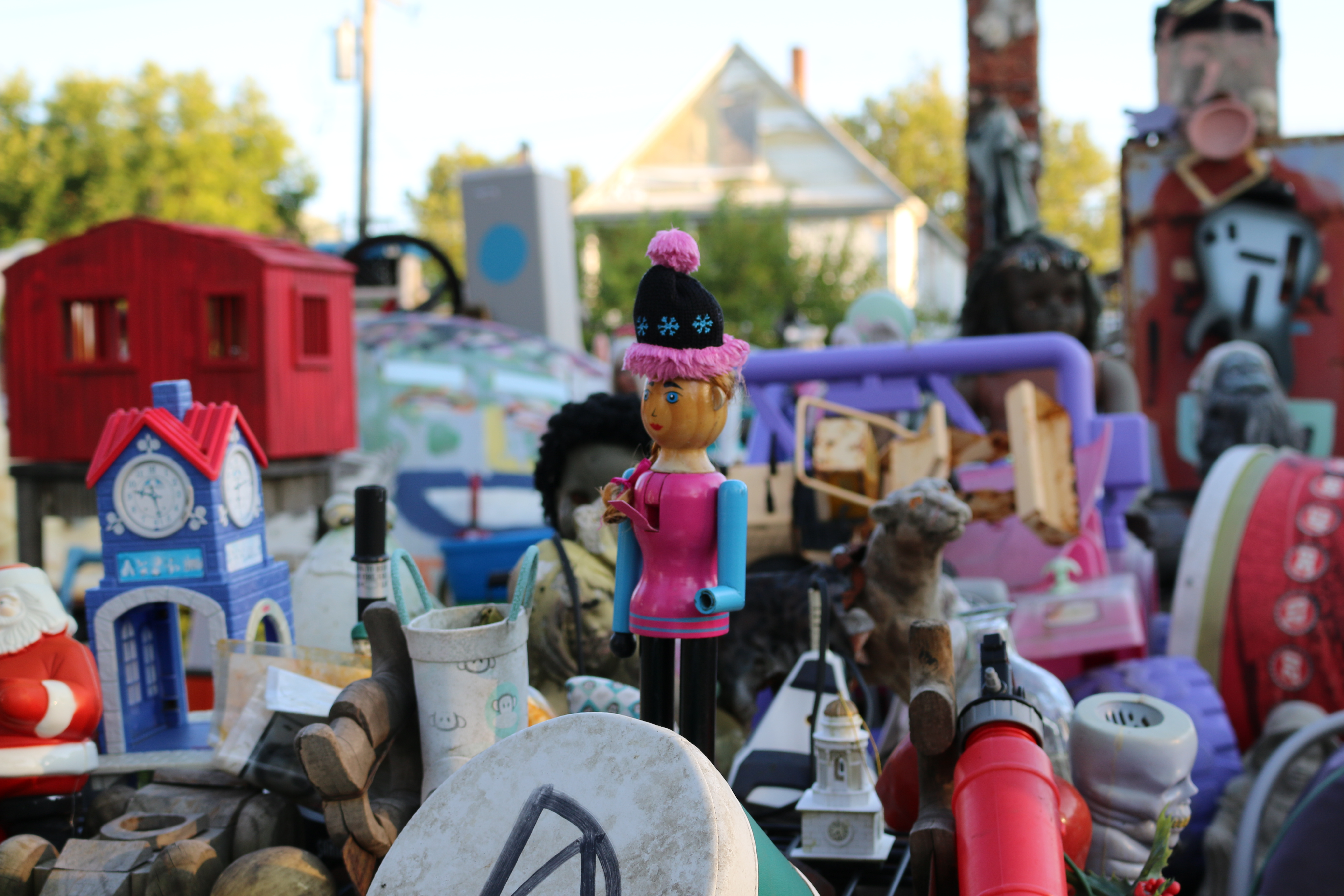 Close up of pink wooden doll with knit cap midst random toys.